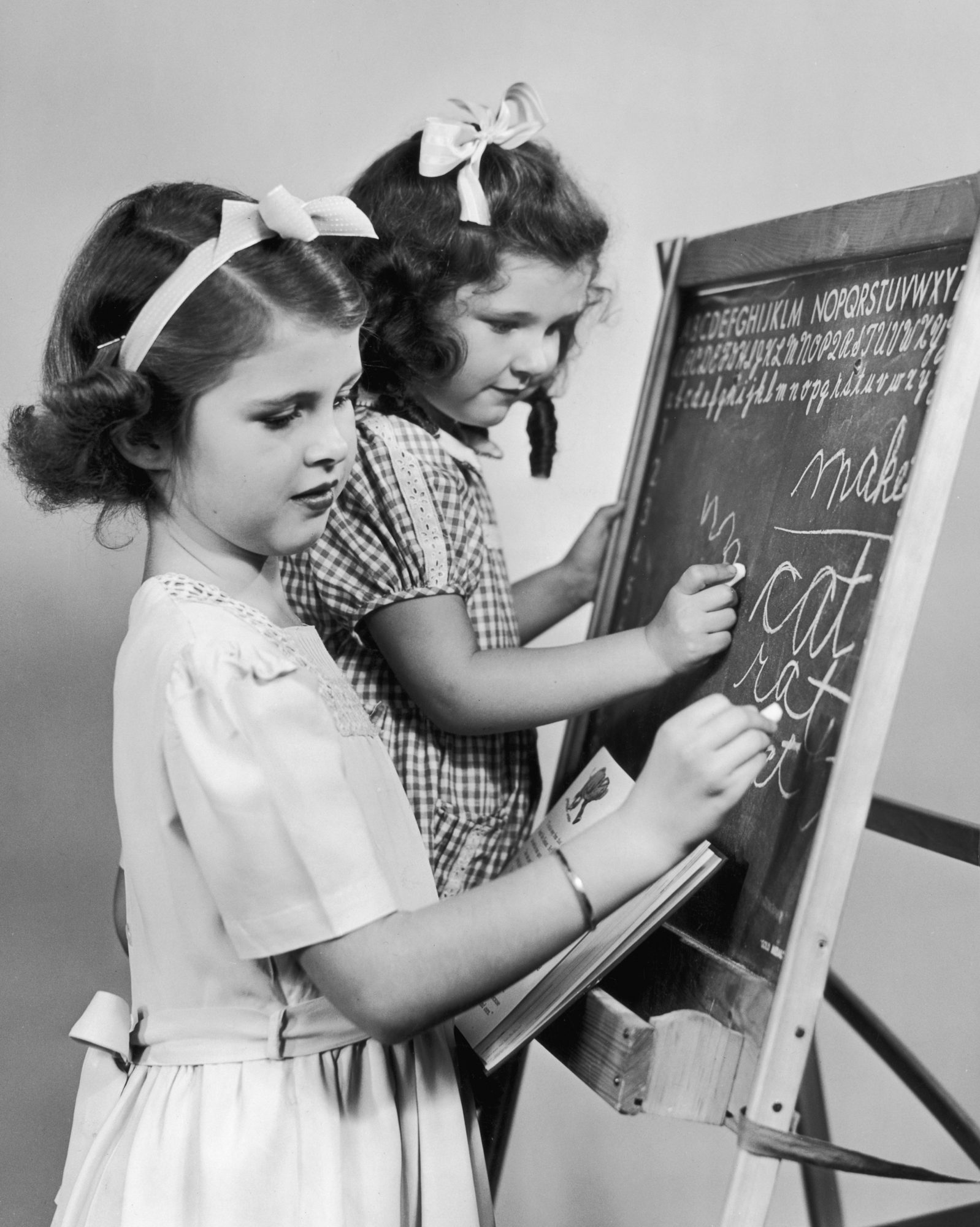 Two Girls Practicing Writing Cursive on Blackboard