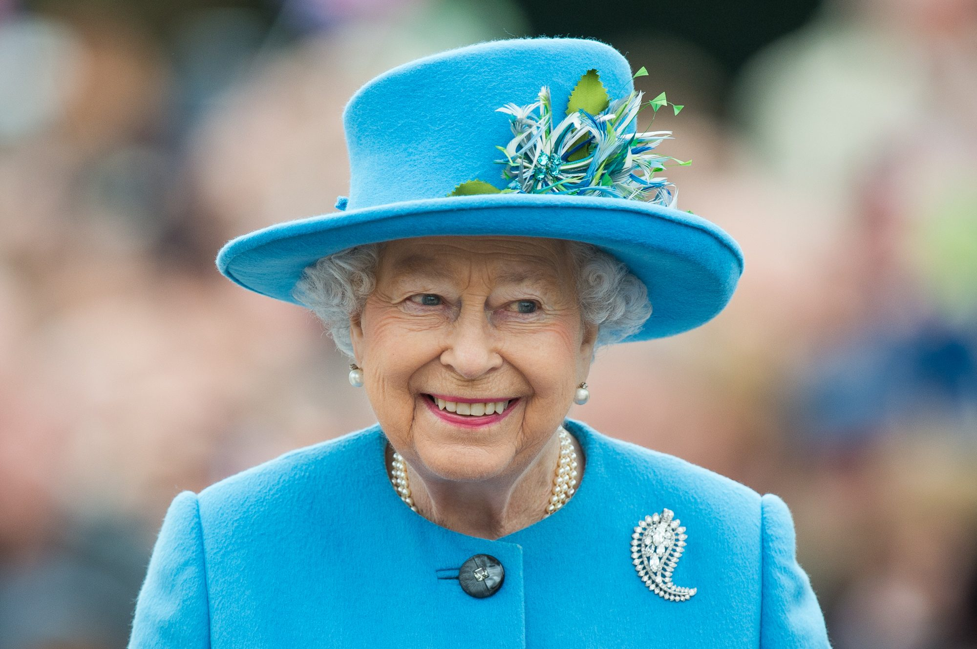 queen Elizabeth smiling wearing blue
