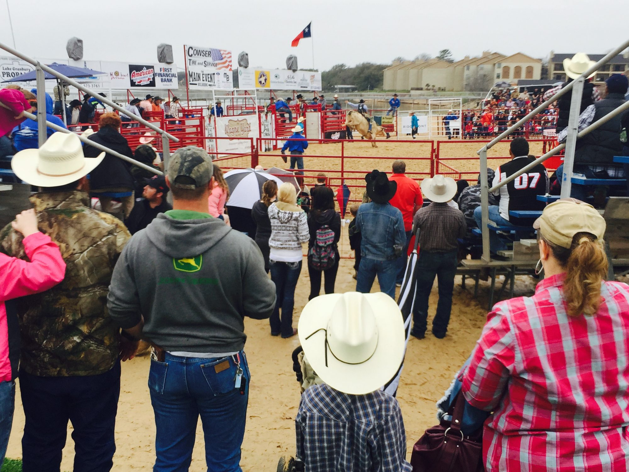 Crowd watching a cowboy ride a bull, Granbury, Texas.