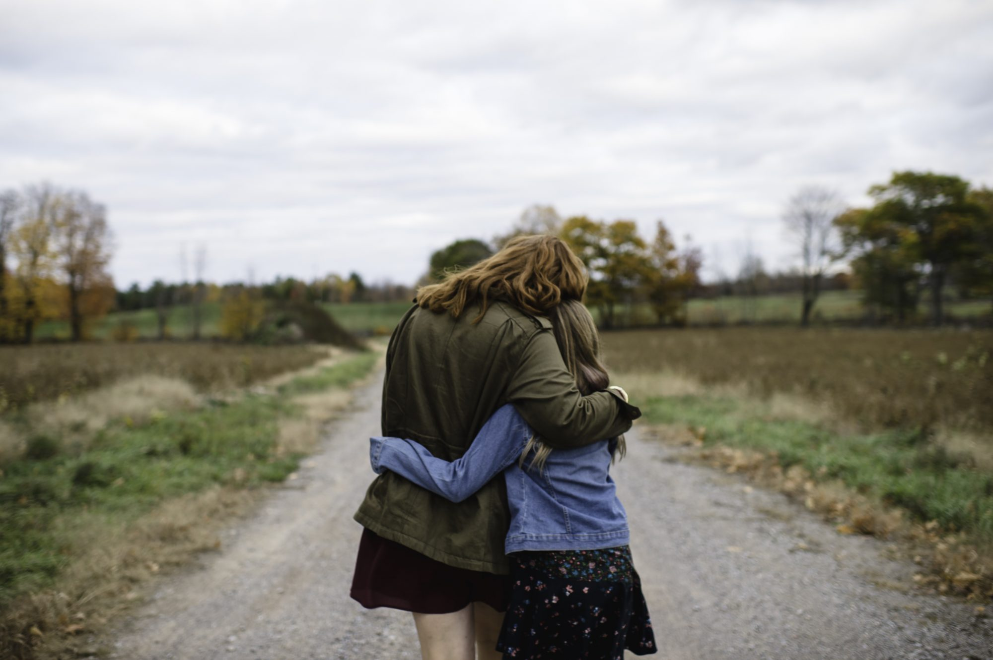 Mother and daughter hugging on dirt road, Lakefield, Ontario, Canada