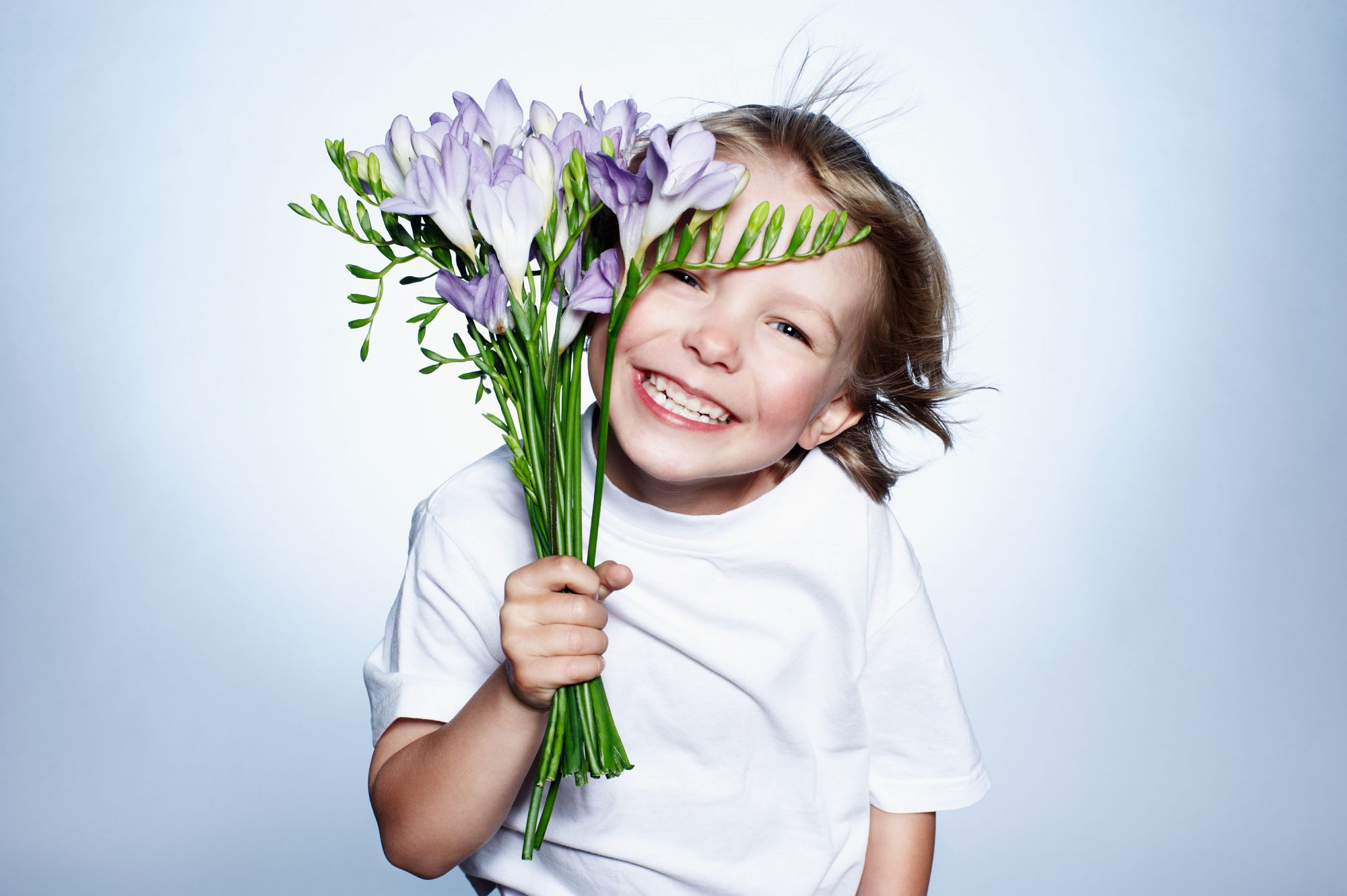Little Boy Smiling with Flowers