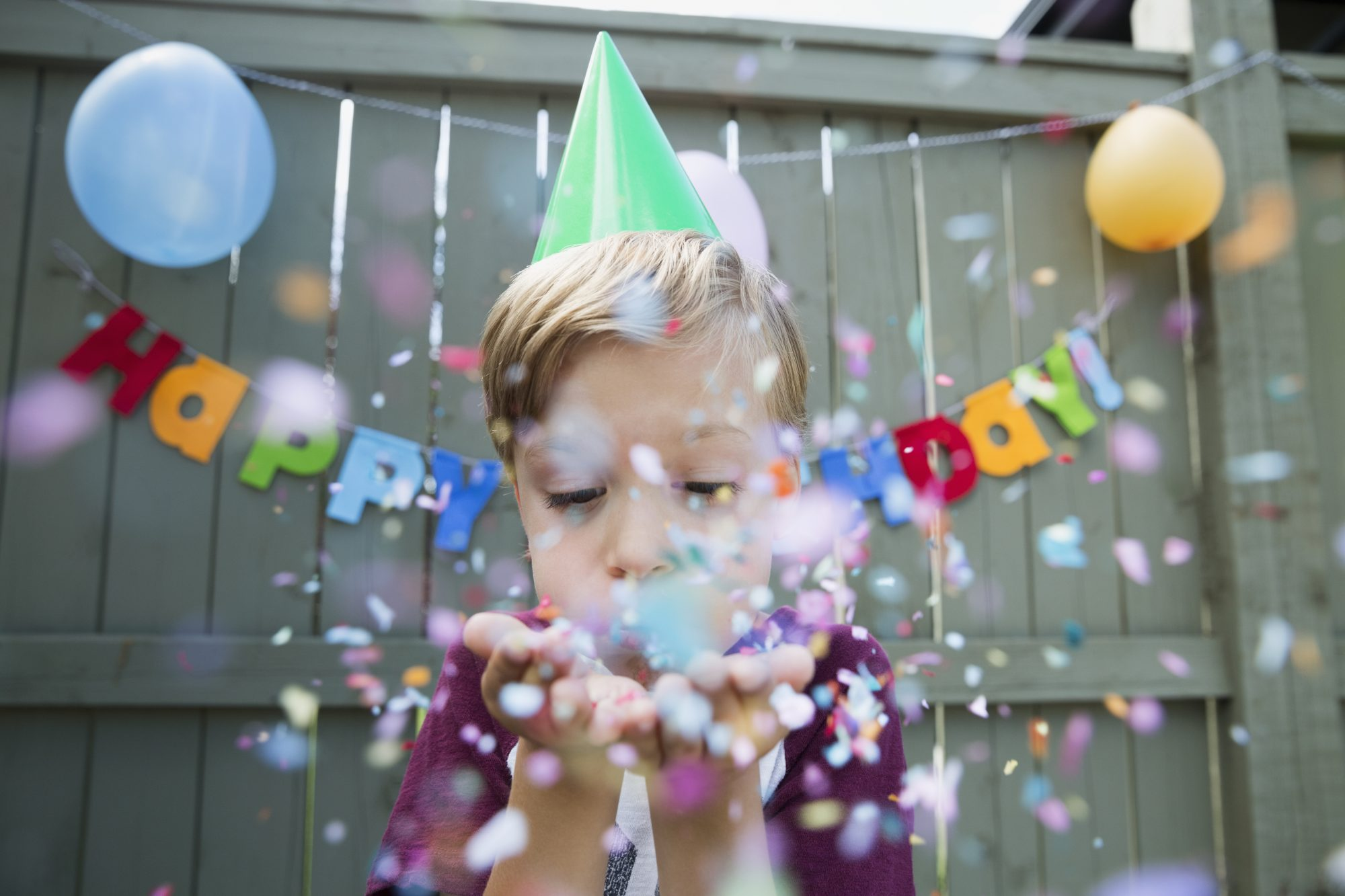 Young Boy Blowing Birthday Confetti