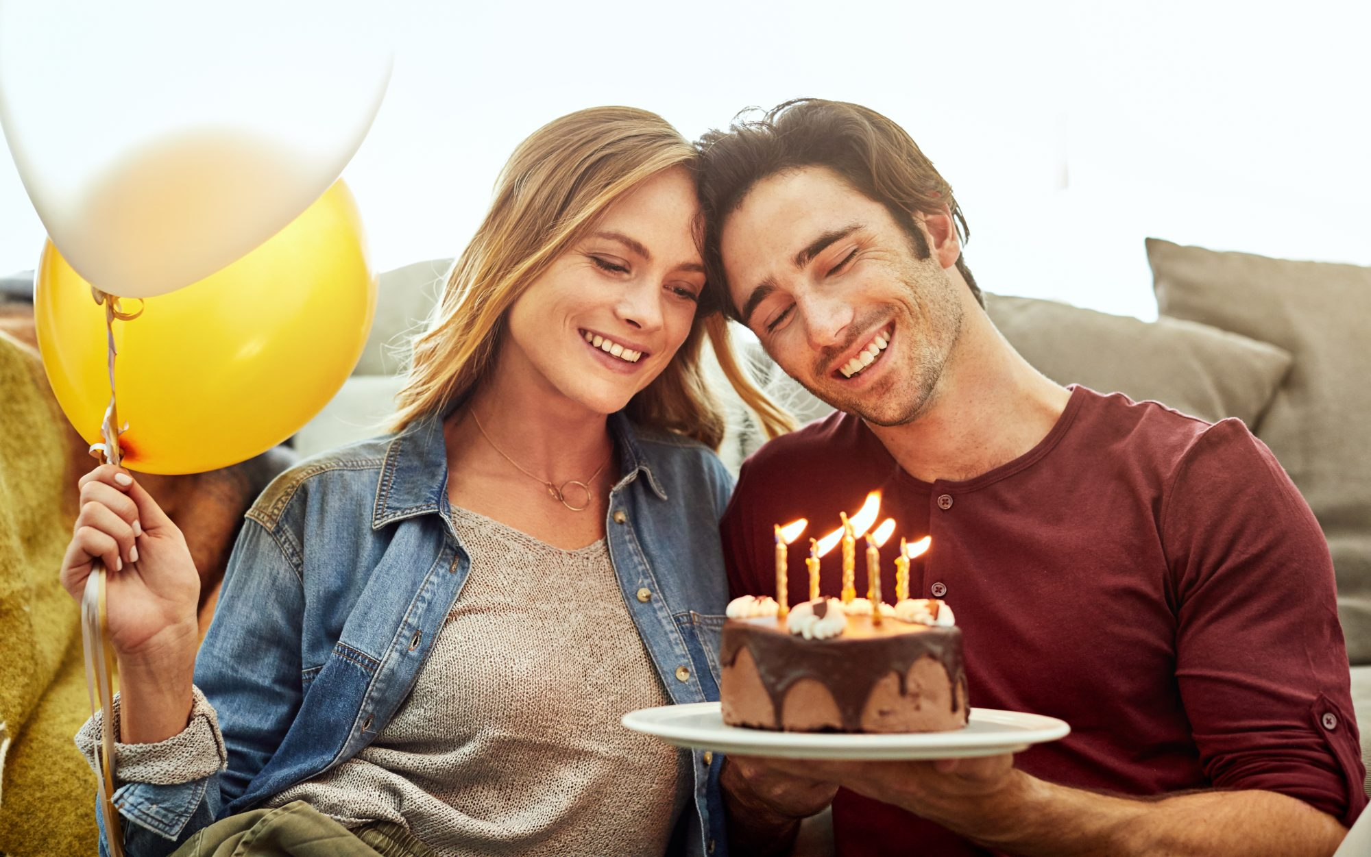 Young Couple Sharing Birthday Cake with Balloons