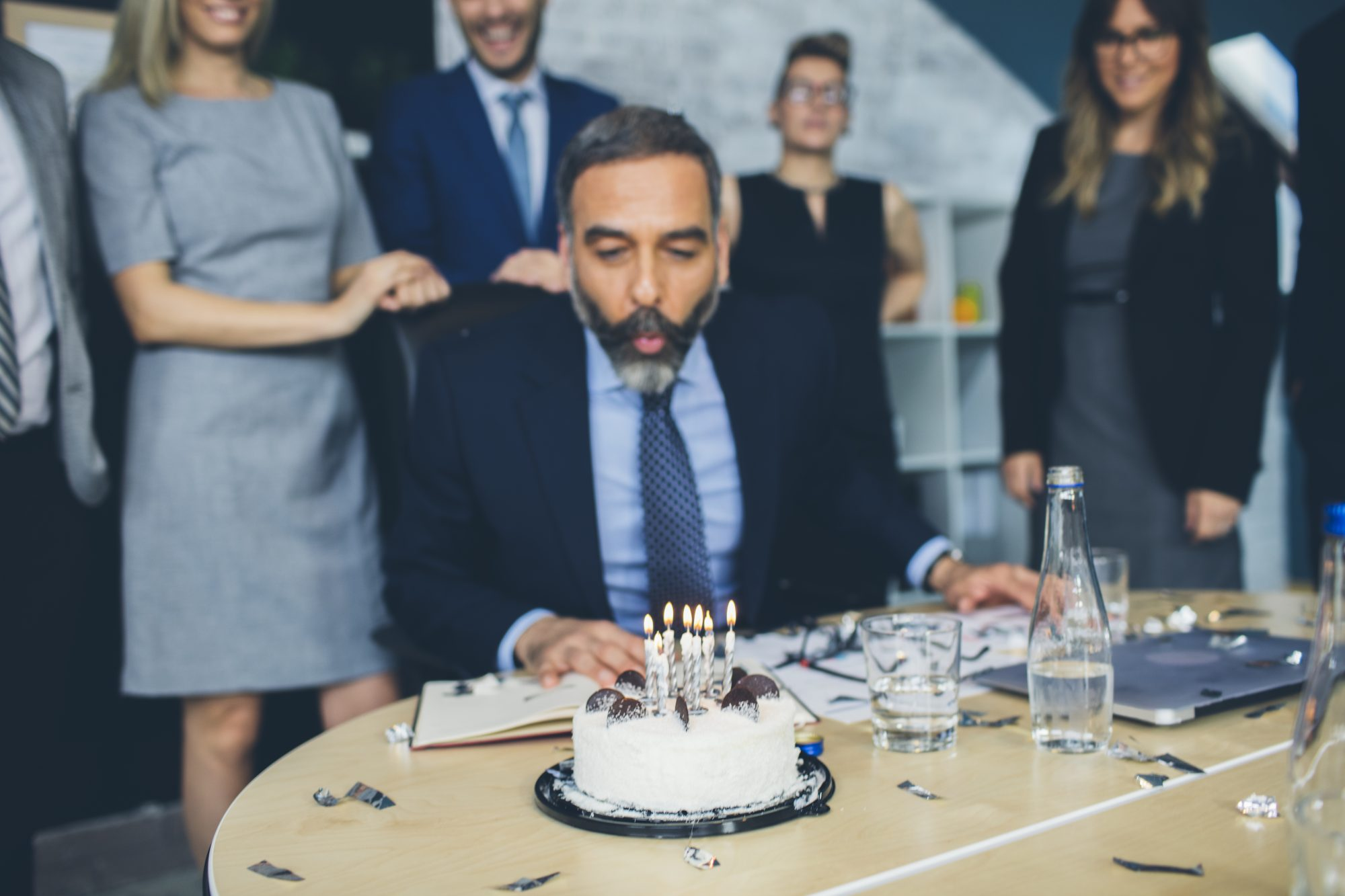 Man Blowing Birthday Candles in Office