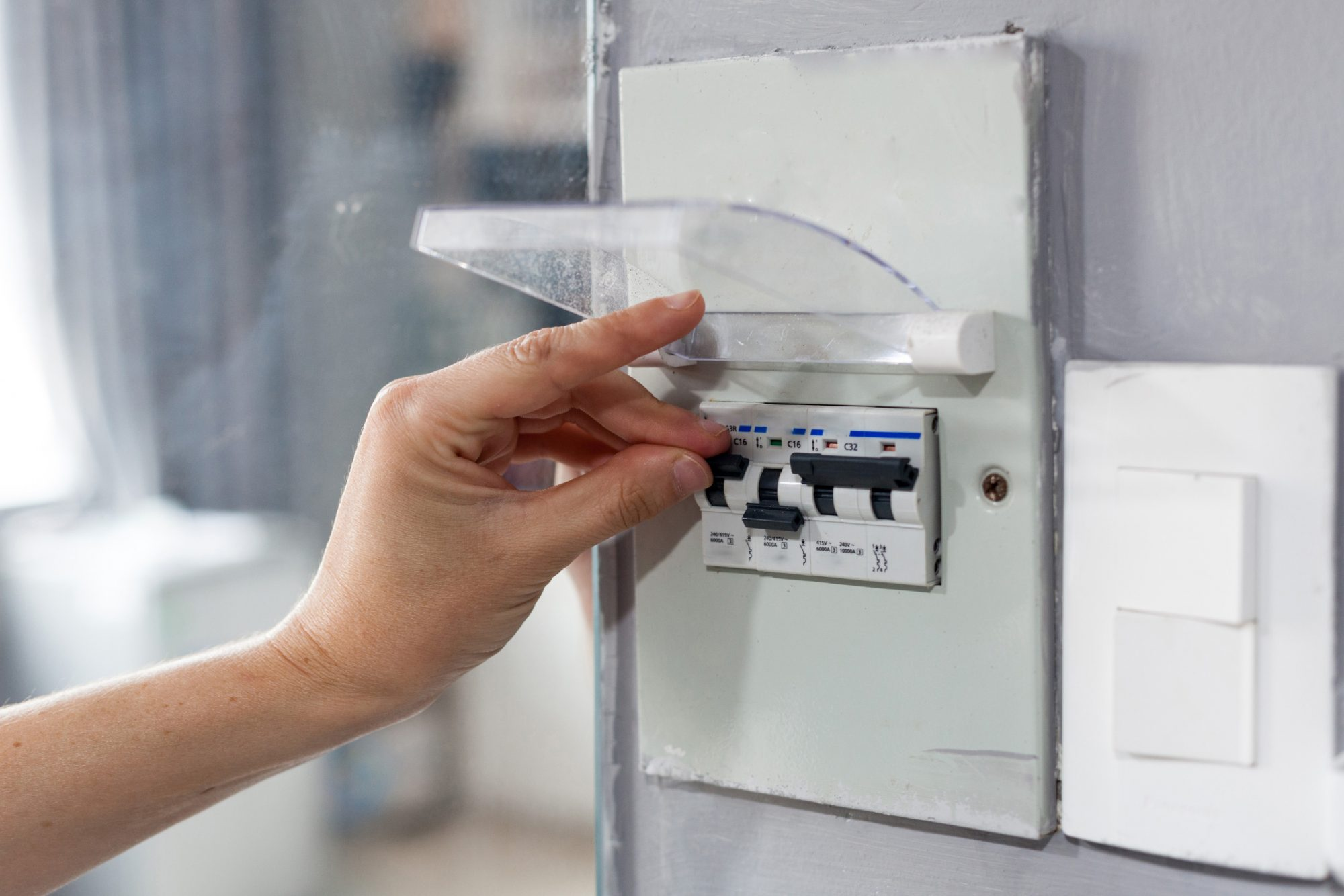 Woman hand turning off fuse box in the house