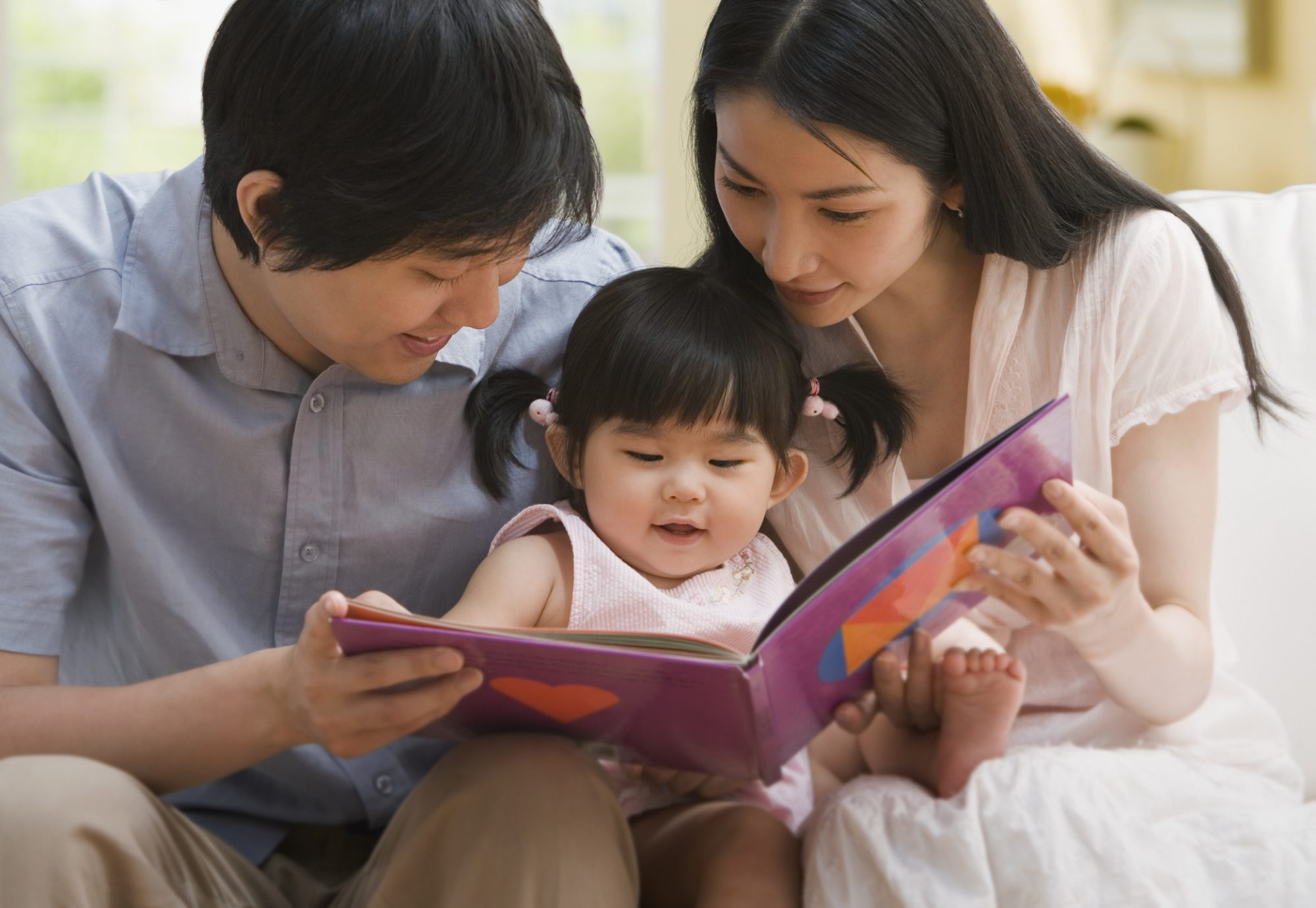 Parents Reading to Baby Daughter
