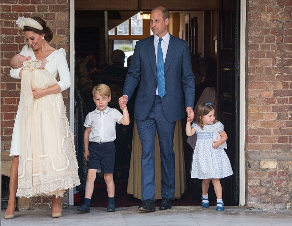 Britain's Princess Charlotte of Cambridge and Britain's Prince George of Cambridge hold hands with their father, Britain's Prince William, Duke of Cambridge, as Britain's Prince Louis of Cambridge is carried by his mother, Britain's Catherine, Duchess ...