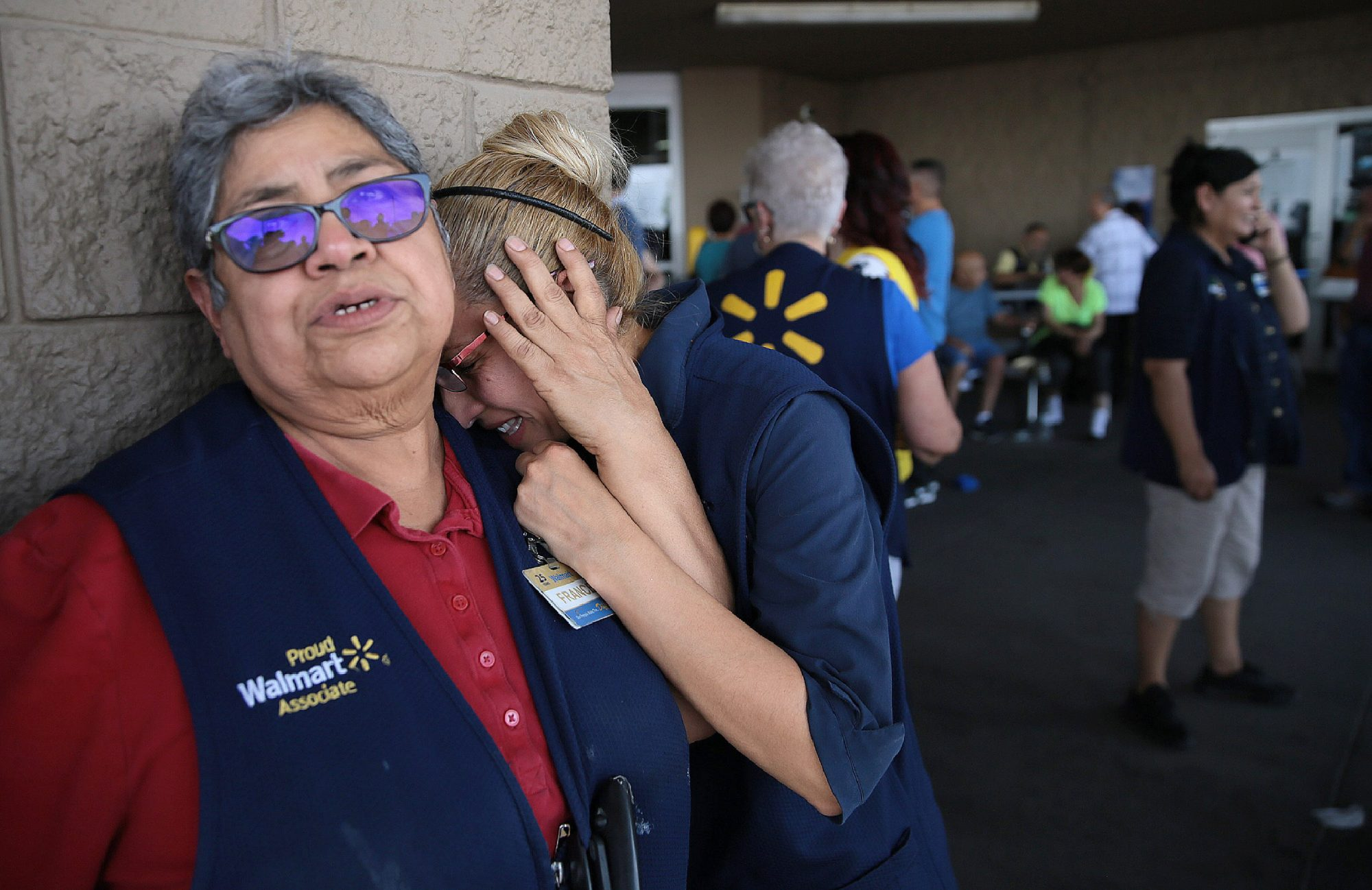 Walmart employees react after a shooter opened fire at the store at Cielo Vista Mall in El Paso, Texas on August 3, 2019
