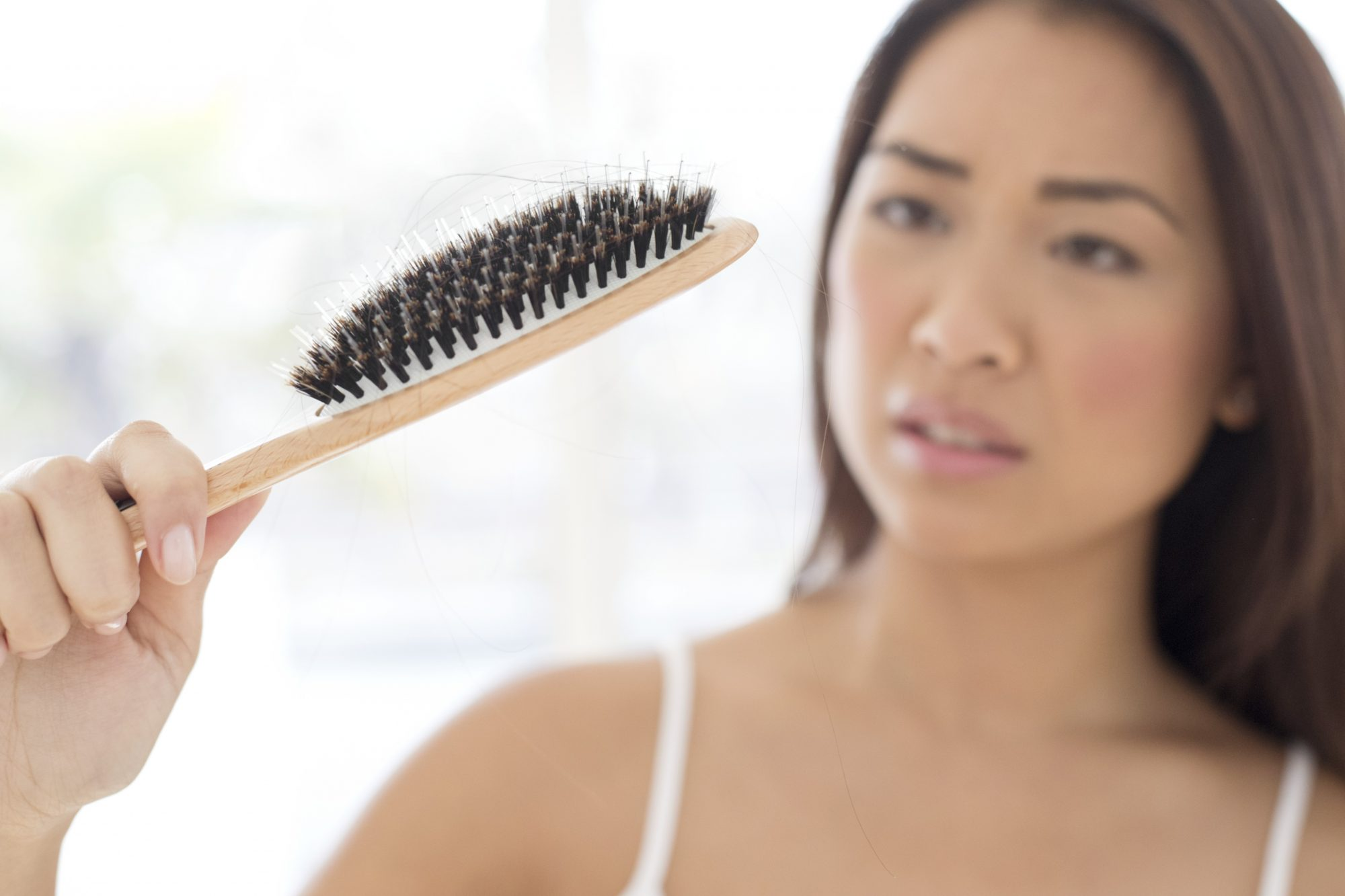 Woman Losing Hair in Brush