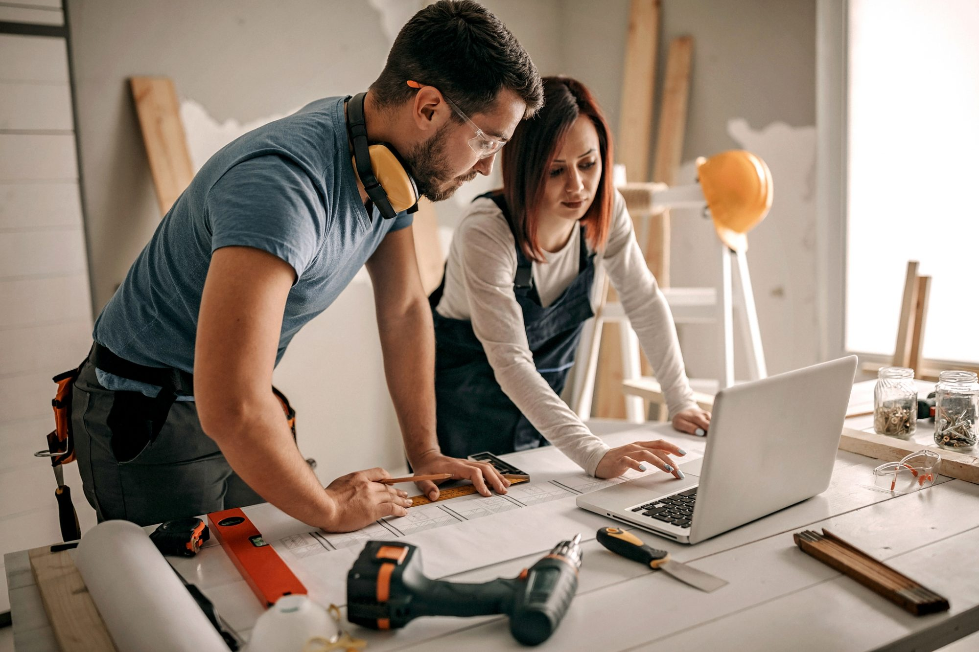 Man and Woman Look at Renovation Plans on Laptop
