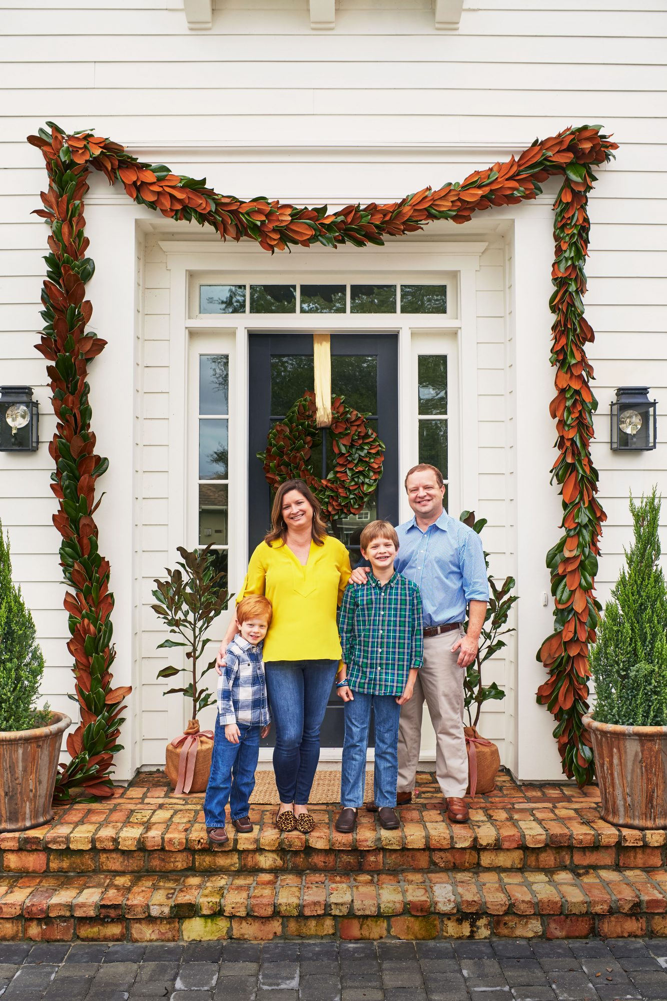 Andrew Howard with Family in front of house decorated for Christmas
