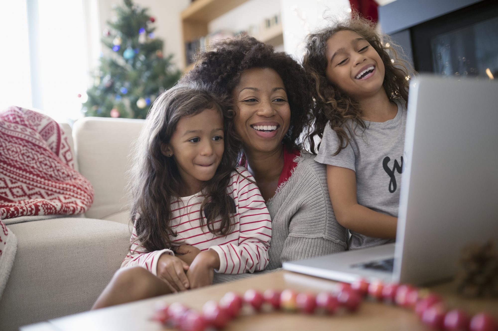Laughing mother and daughters video chatting at laptop in Christmas living room
