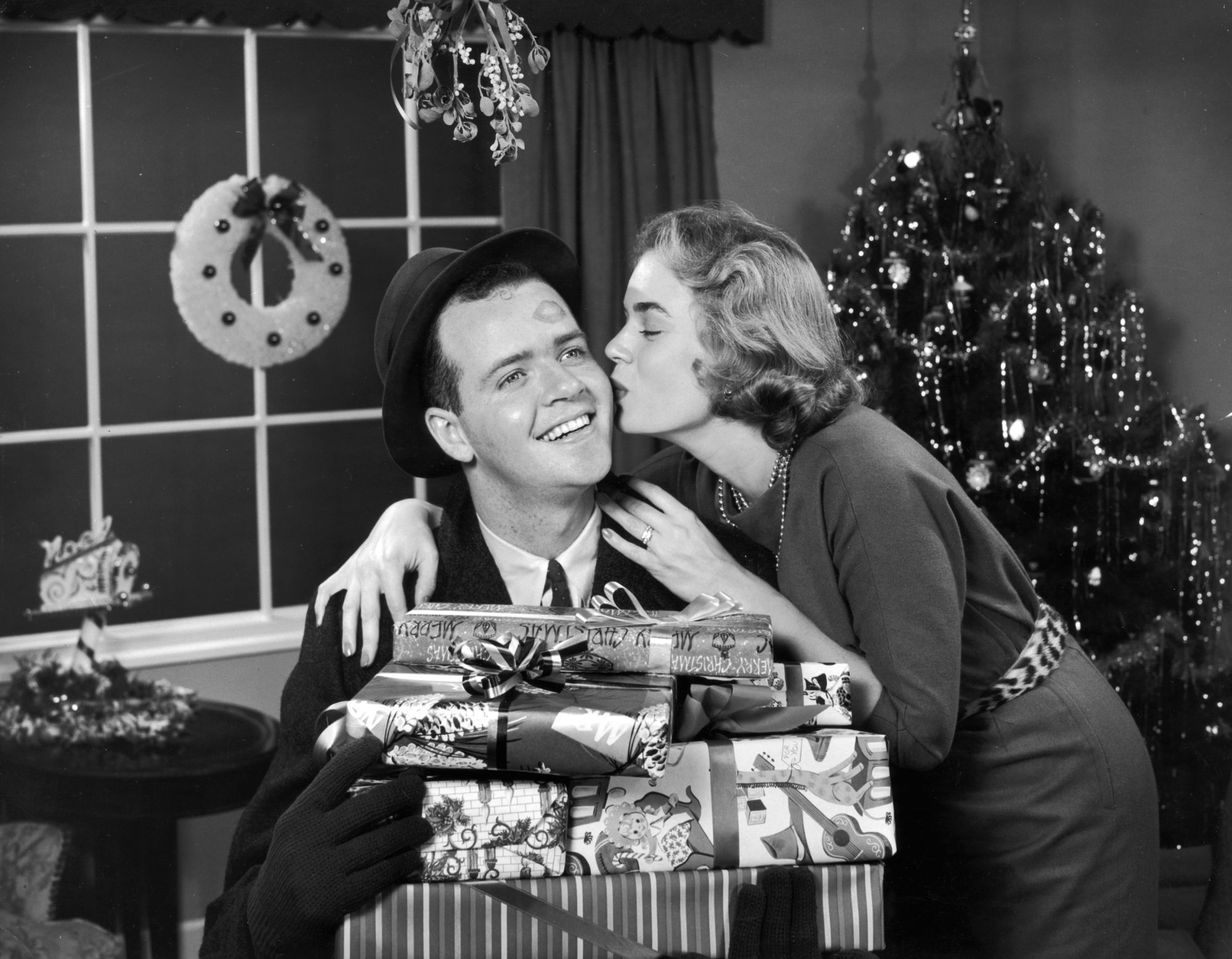 Woman Kissing Man Under Mistletoe