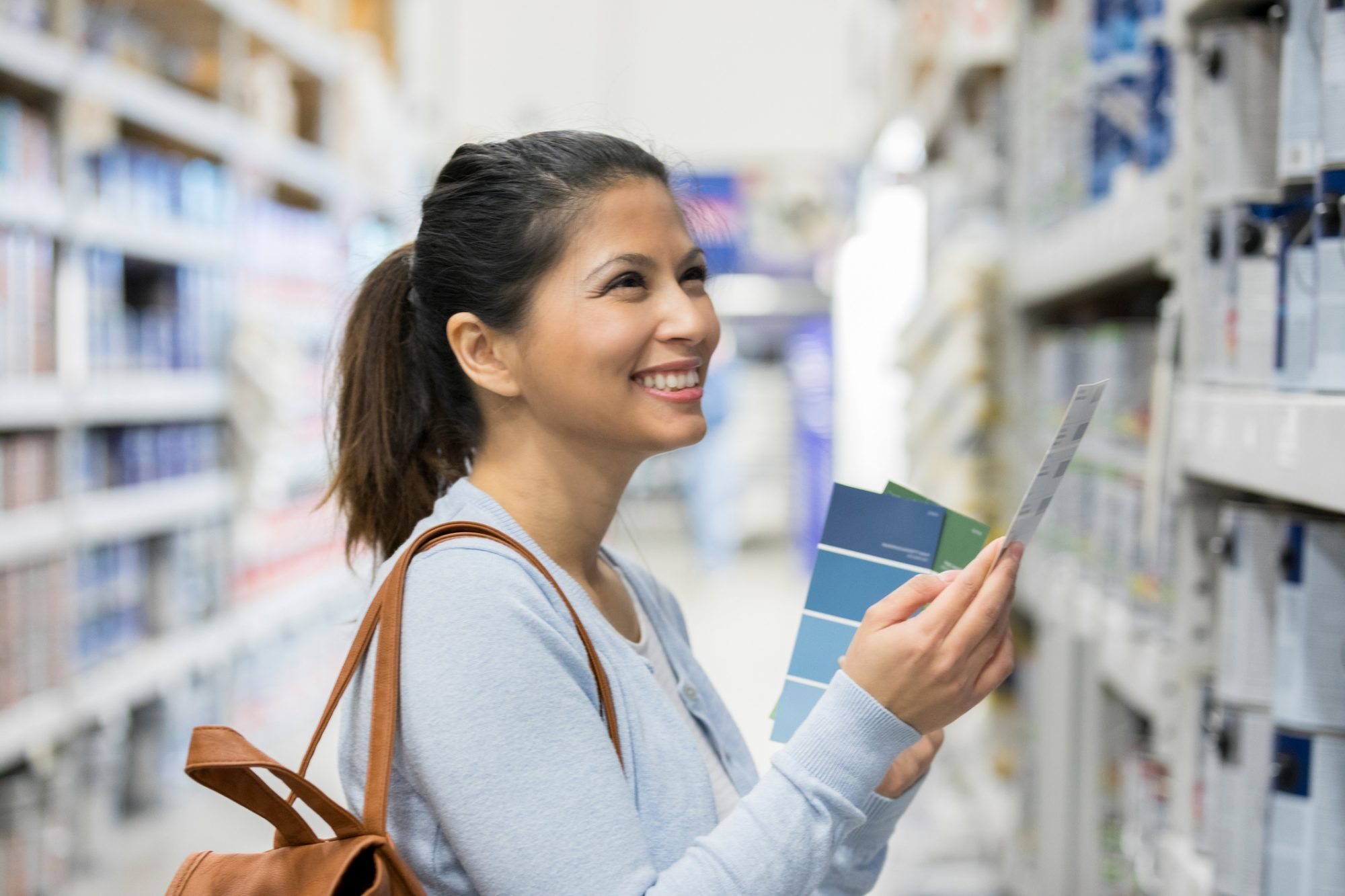 Woman in Paint Aisle Picking Out Colors