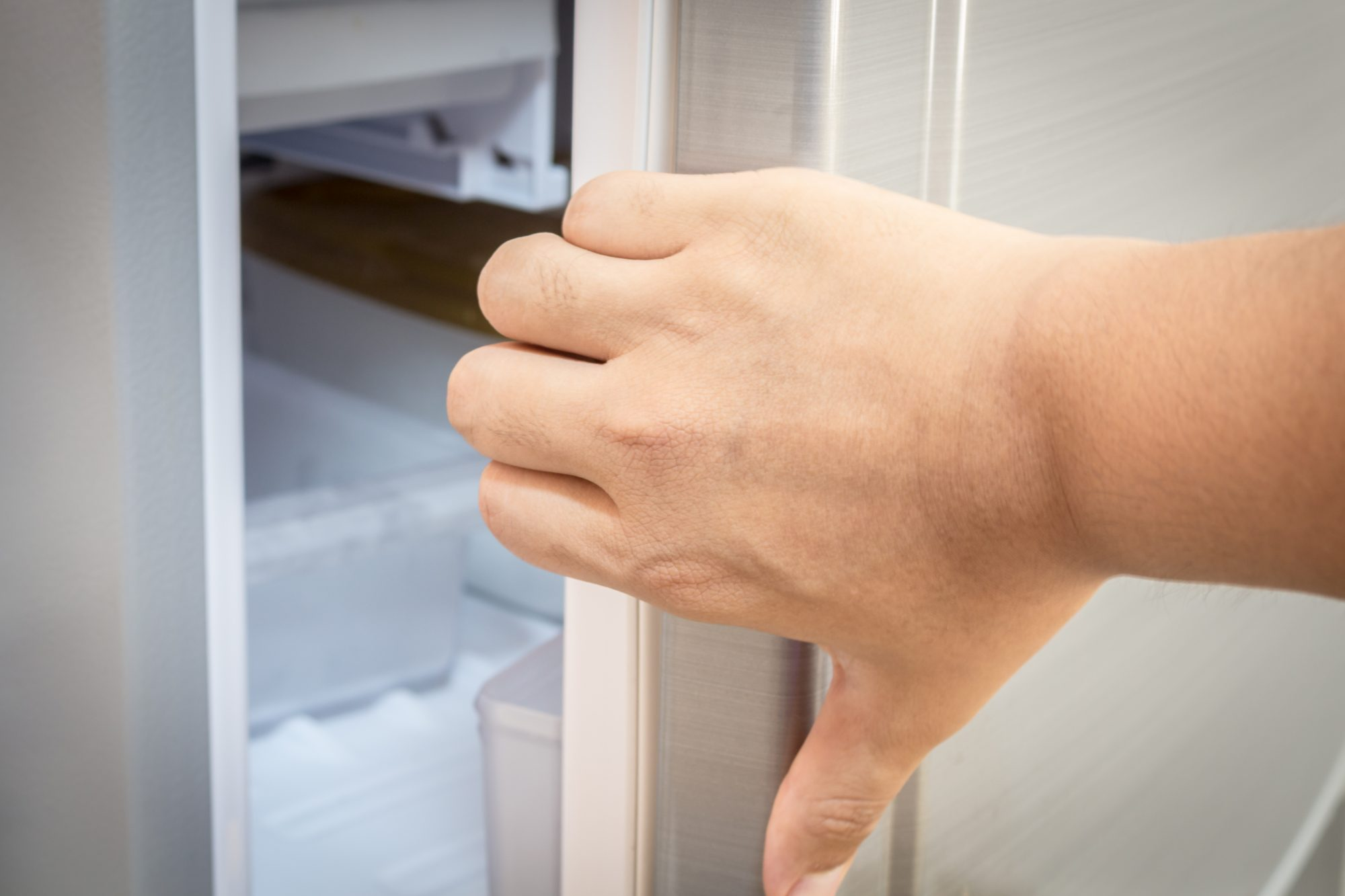 Close-Up Of Woman Opening Refrigerator Door At Home