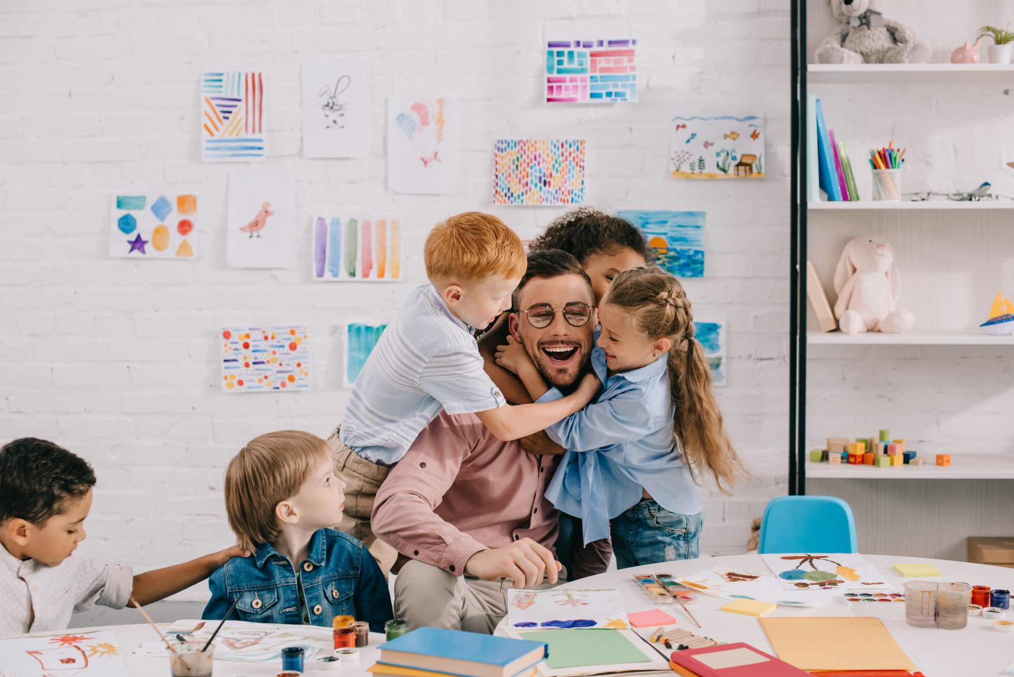 kids hugging happy teacher at table in classroom