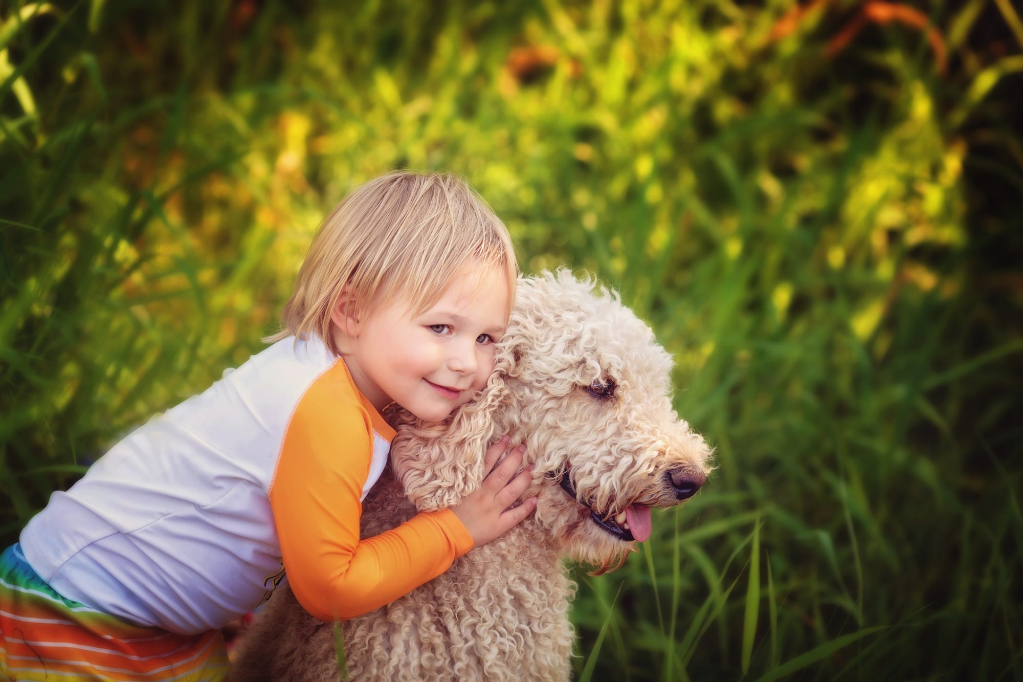 Young Boy Hugging Standard Poodle