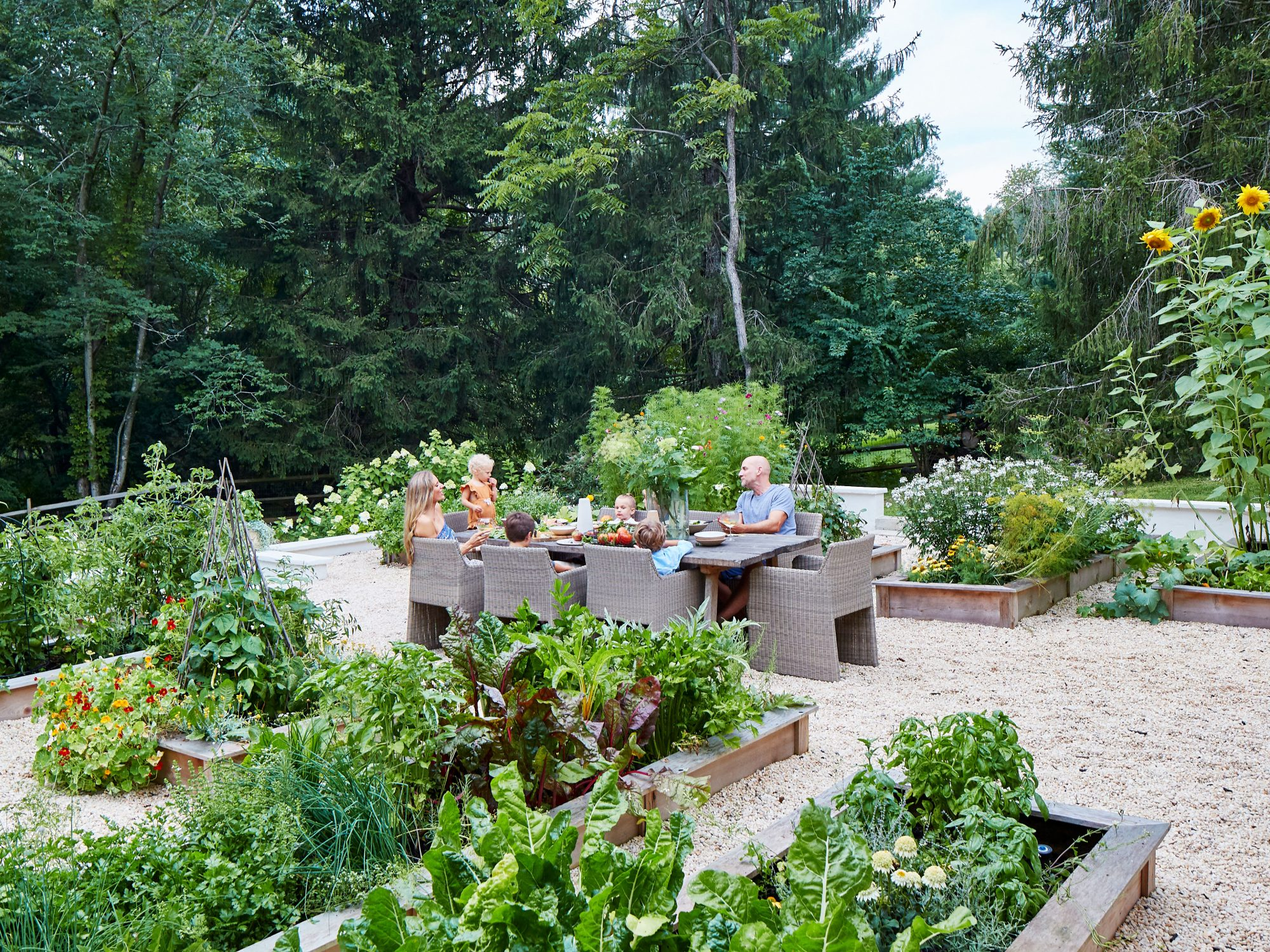 Lauren Liess and Family Eating Dinner at Table in Vegetable Garden