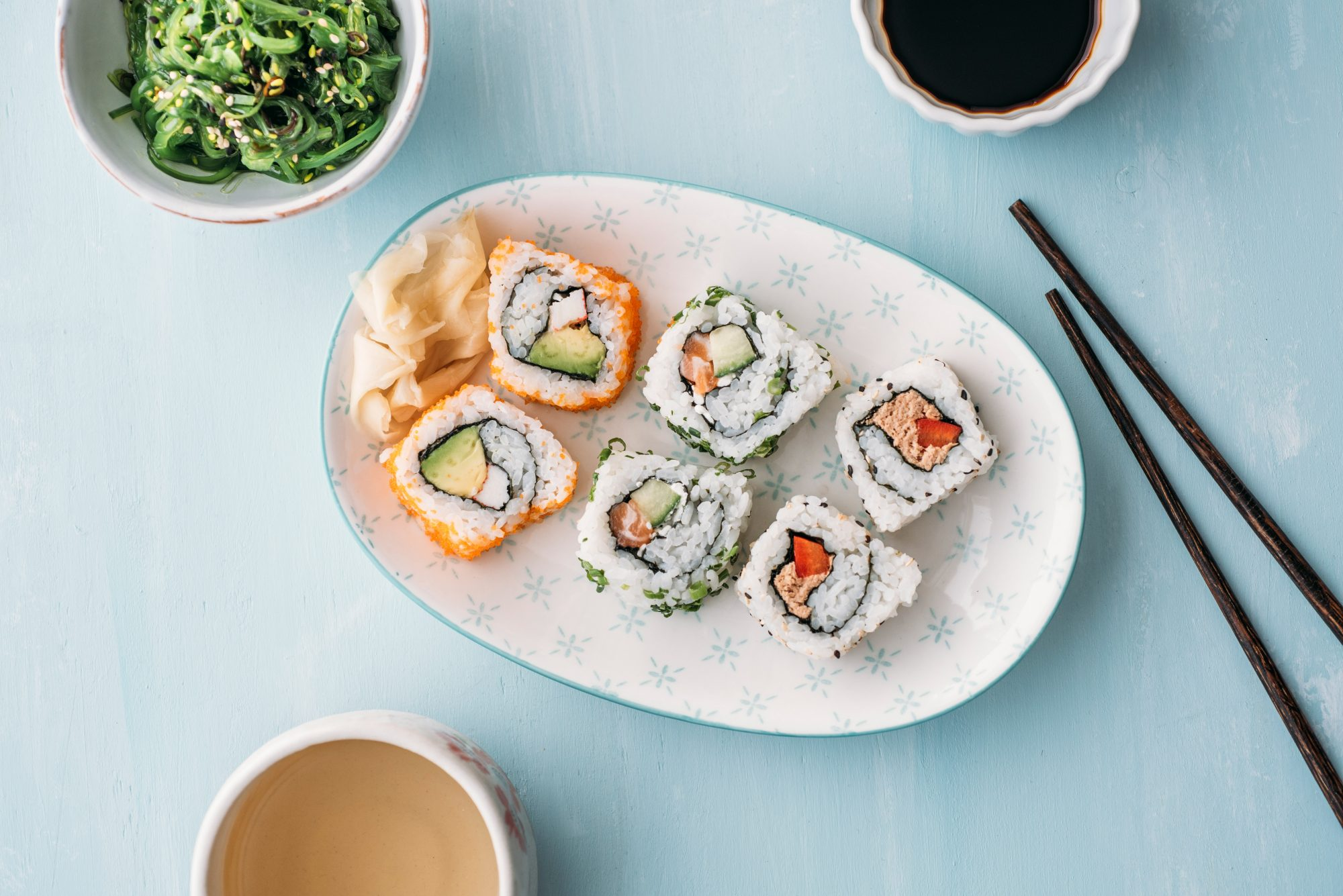 Sushi rolls on plate with green tea
