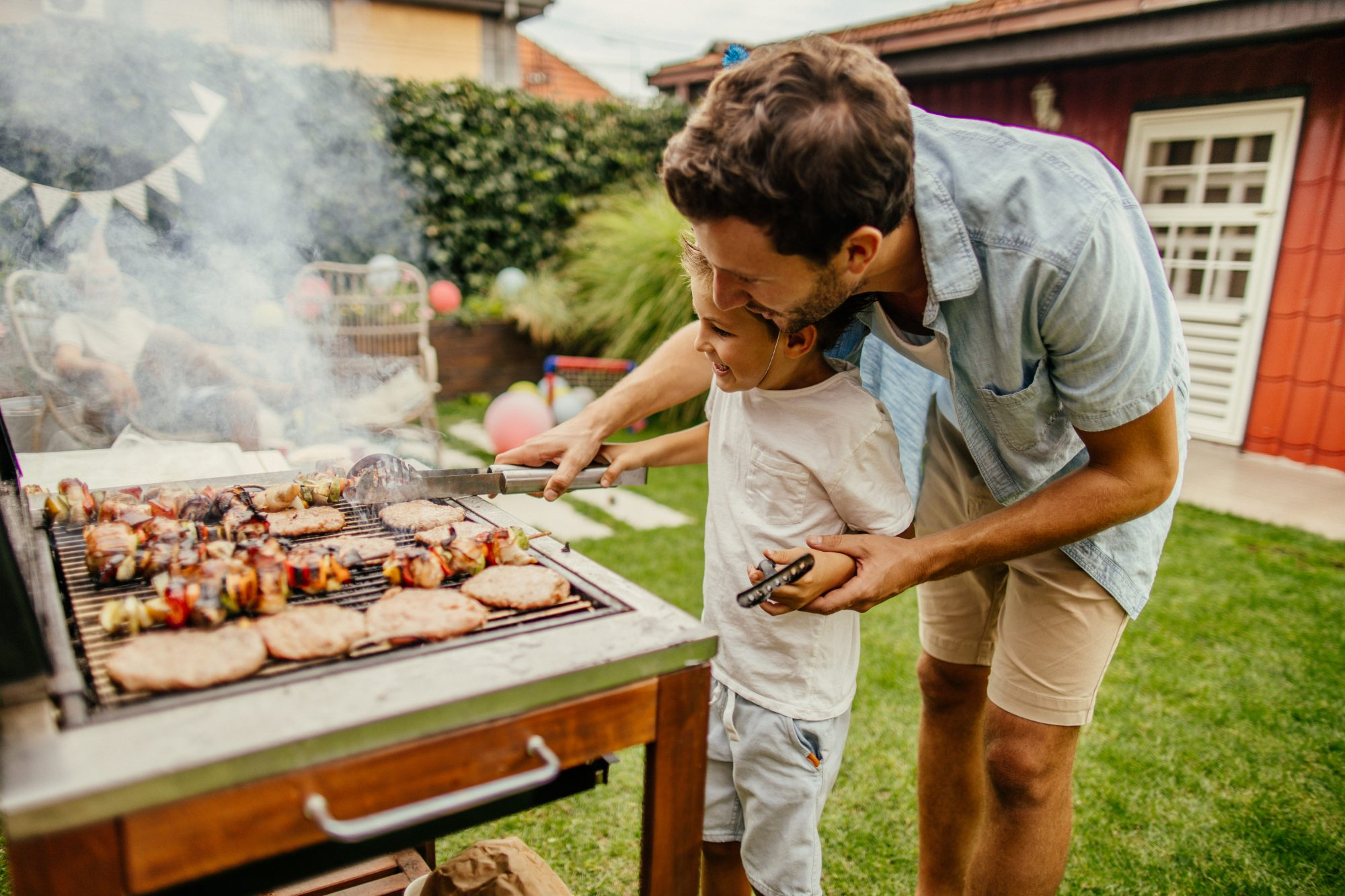 Grilling meat with dad and son