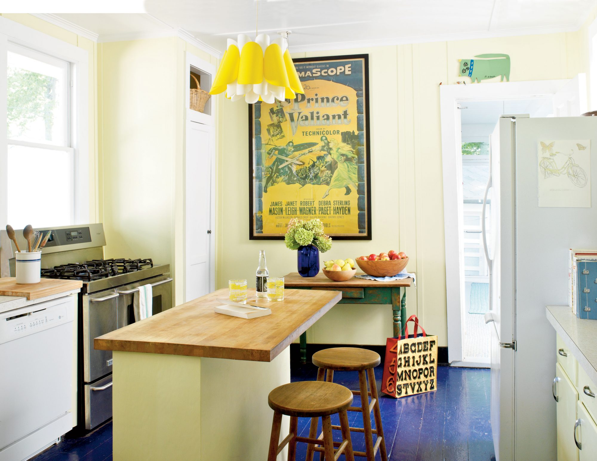 The charm of this lakeside cottage kitchen lies in its attention to detail. The previously linoleum-covered floors were ripped up in favor of this rich blue color, echoed again in a vase of hydrangeas. An ultramodern light fixture paired with the old-school movie poster is a refreshing mix of old and new.