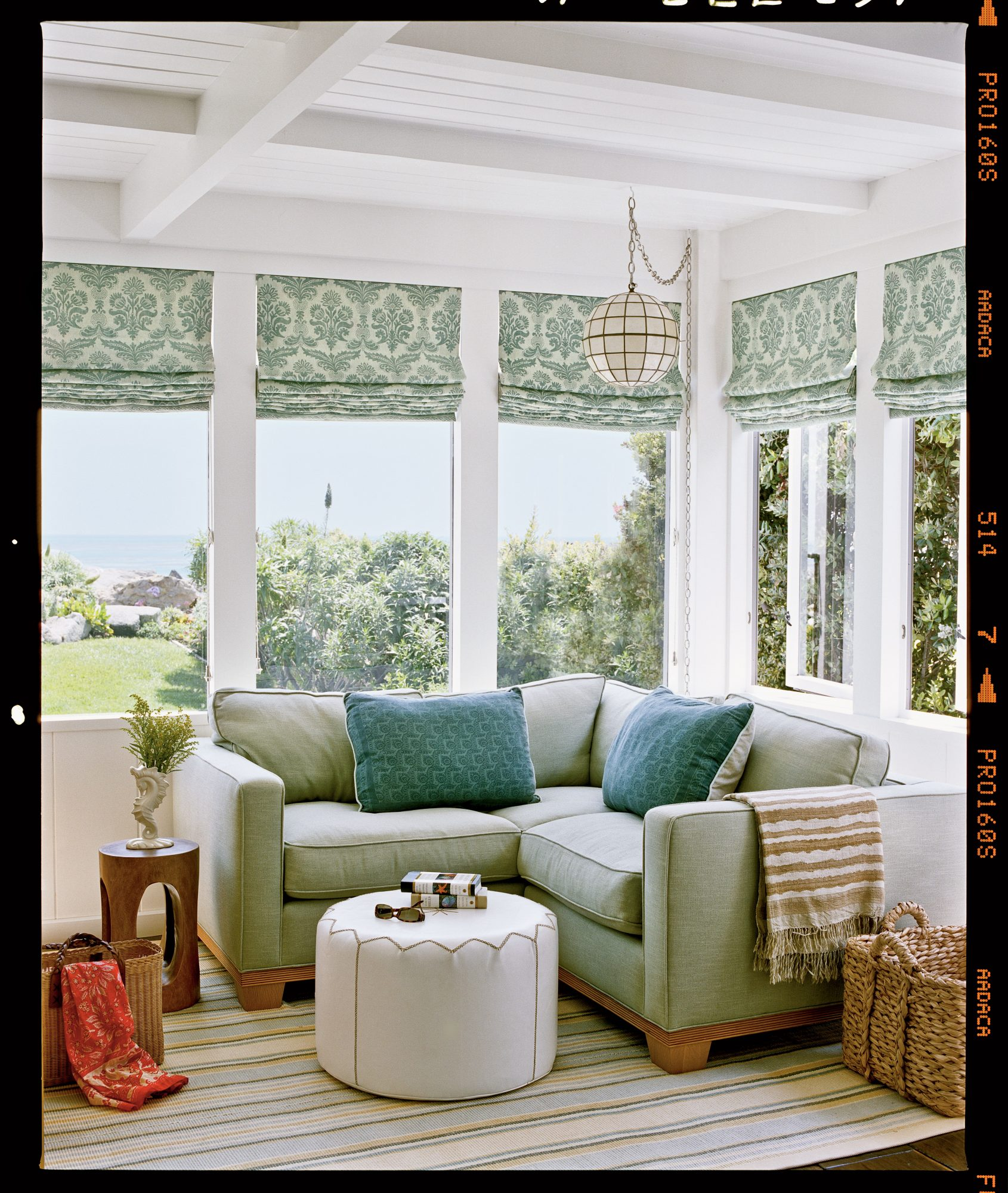 This custom sectional piece in a soothing moss green hue fits snugly into a window-filled corner of this room. A stylish large-scale pattern like this traditional damask lends a feeling of warmth to any room.