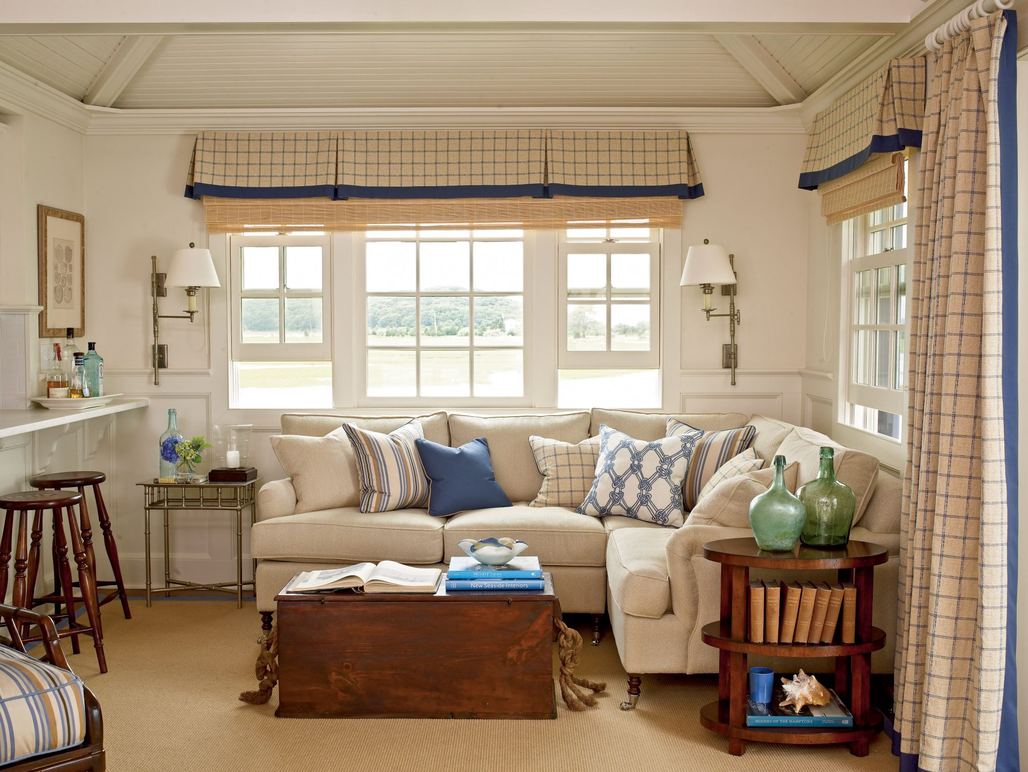 Without the pops of cobalt blue, this smart seating area's neutral tones would feel a little washed out. Fun patterned pillows with drapery and flowers to match don't take the focus off the main event, the wraparound water view from the windows.