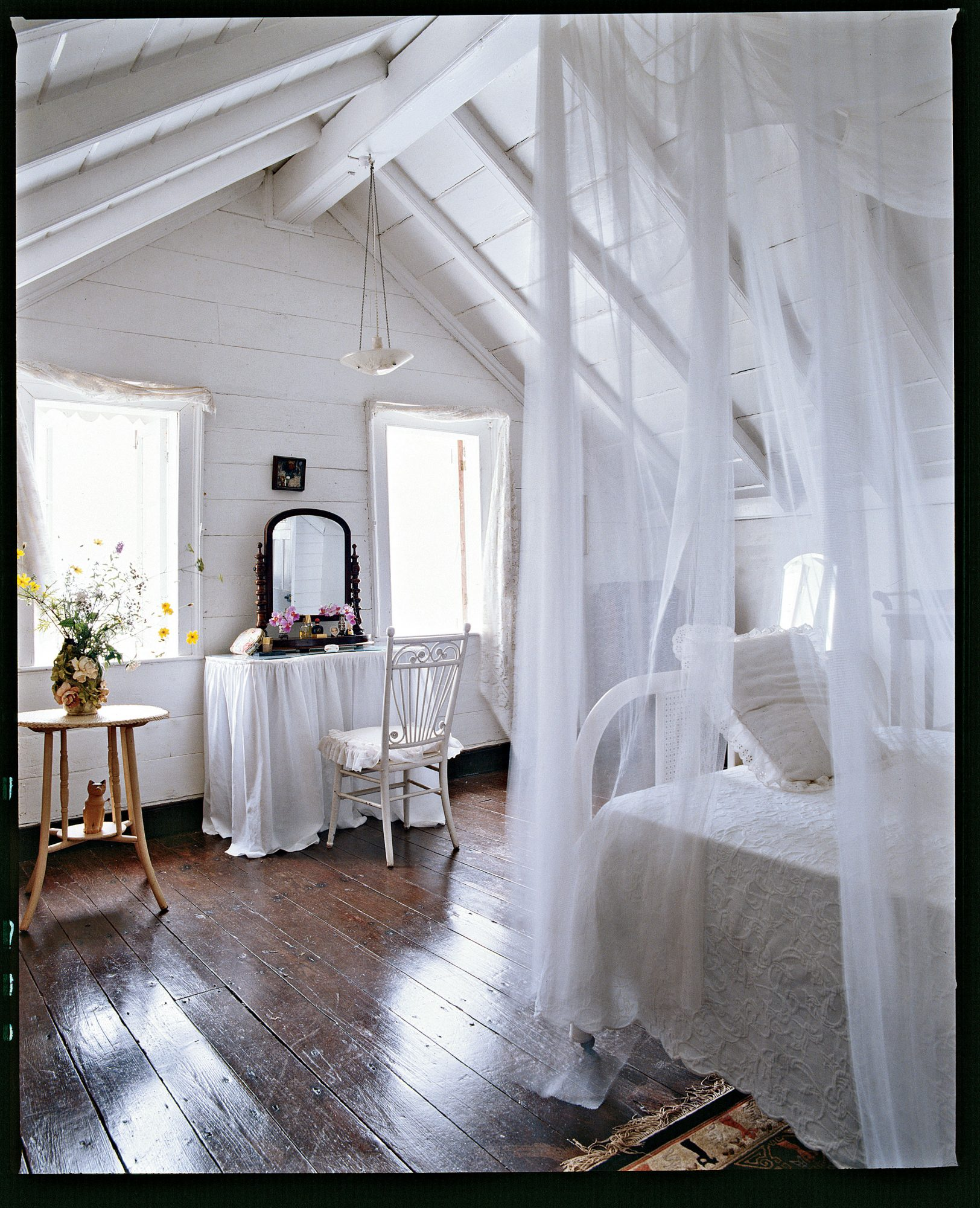 The dramatic high ceilings and mahogany floors in this sparse attic room are timeless. Sheer netting around the bed is a romantic detail that also comes in handy when you leave the windows open on summer nights.