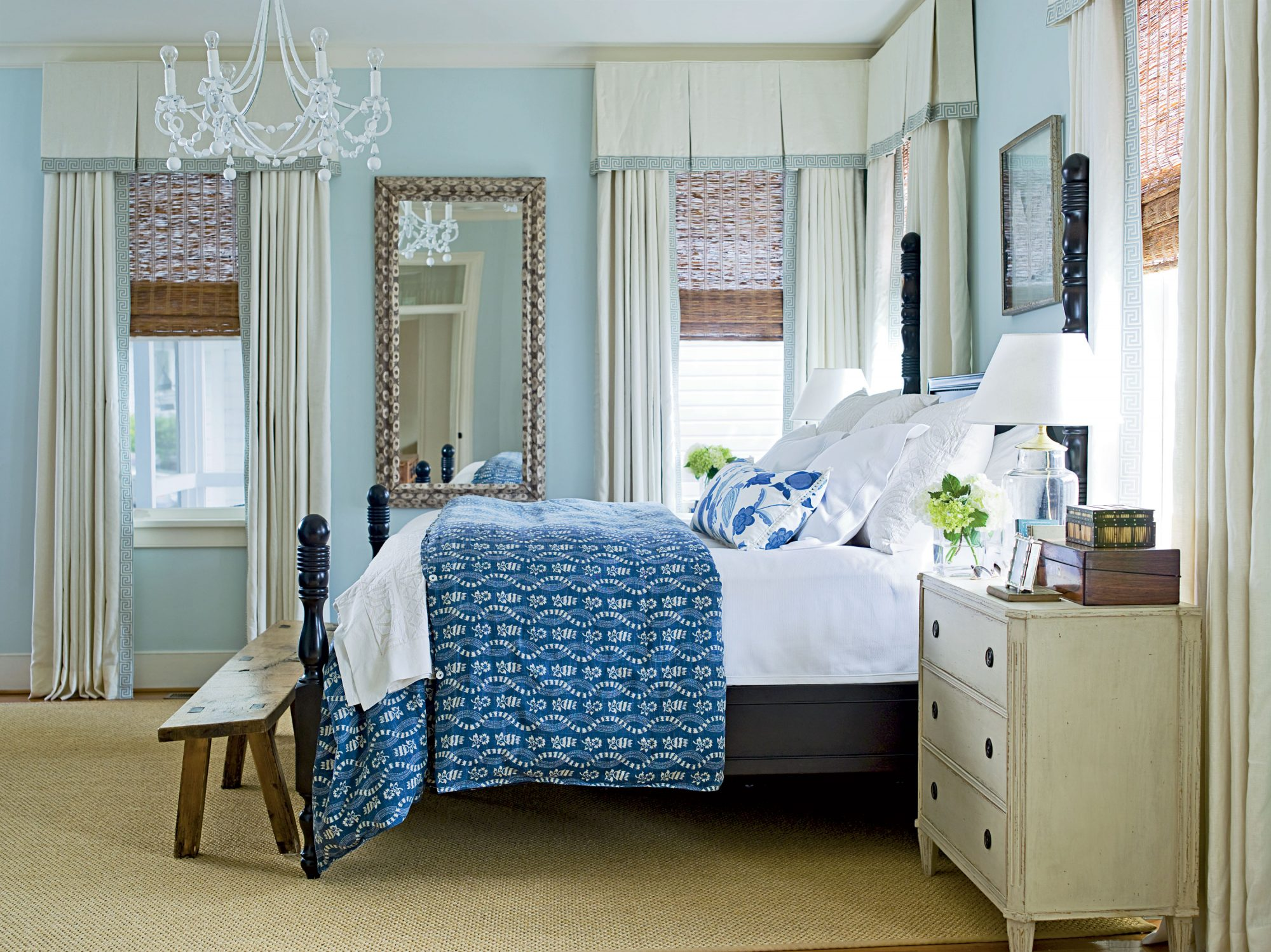 Pay homage to the sea with a bedroom awash with calming blues and ocean accessories such as this mirror framed in oyster shells. A dark wood bed and crisp white chandelier add elegance to the space.