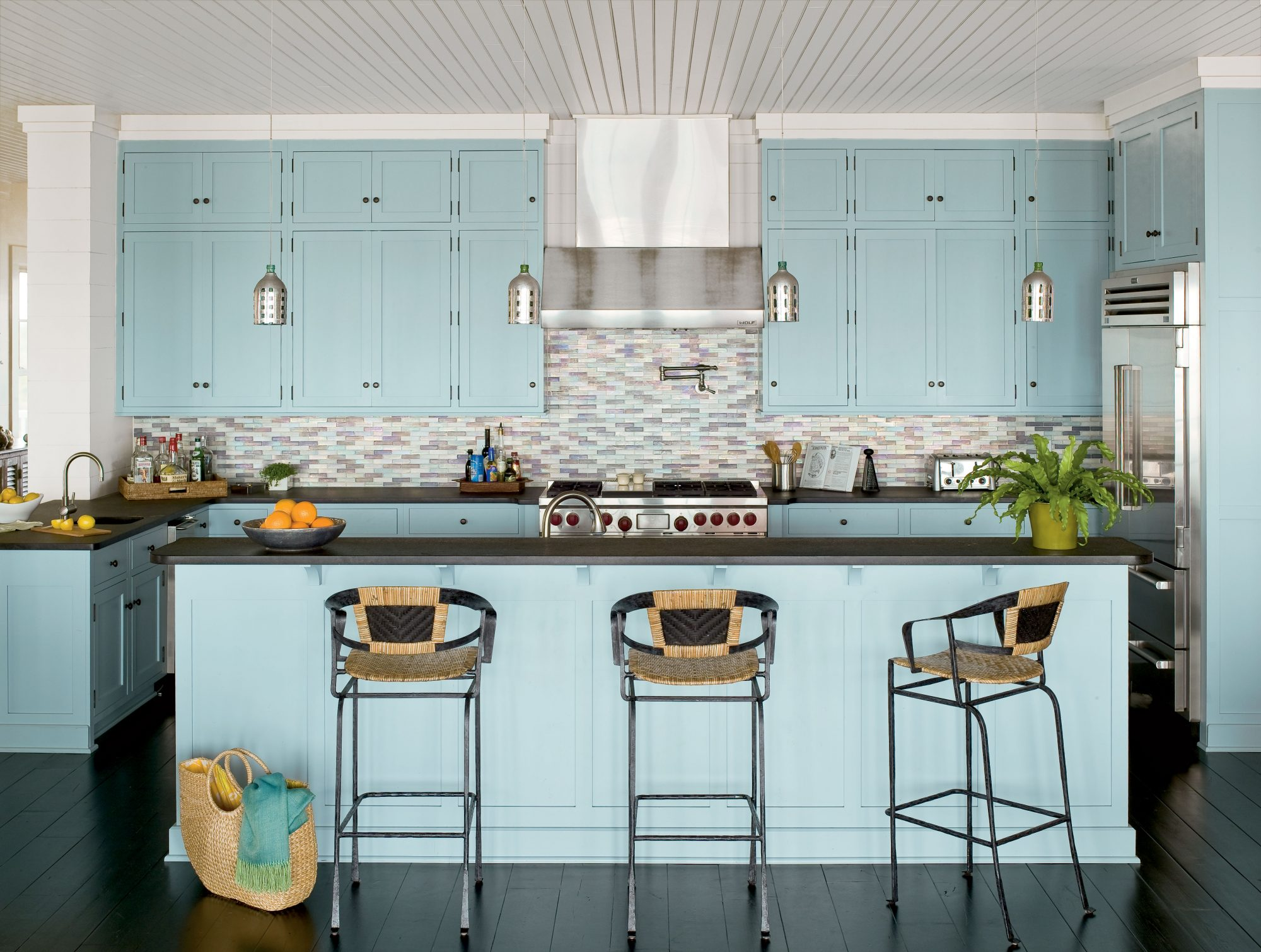 This kitchen's stainless steel appliances and dark surfaces are expertly balanced by the pale blue cabinetry and sea-inspired backsplash. The iridescent tiles in various cerulean shades catch the light beautifully and led to a similar scheme for the rest of the house.