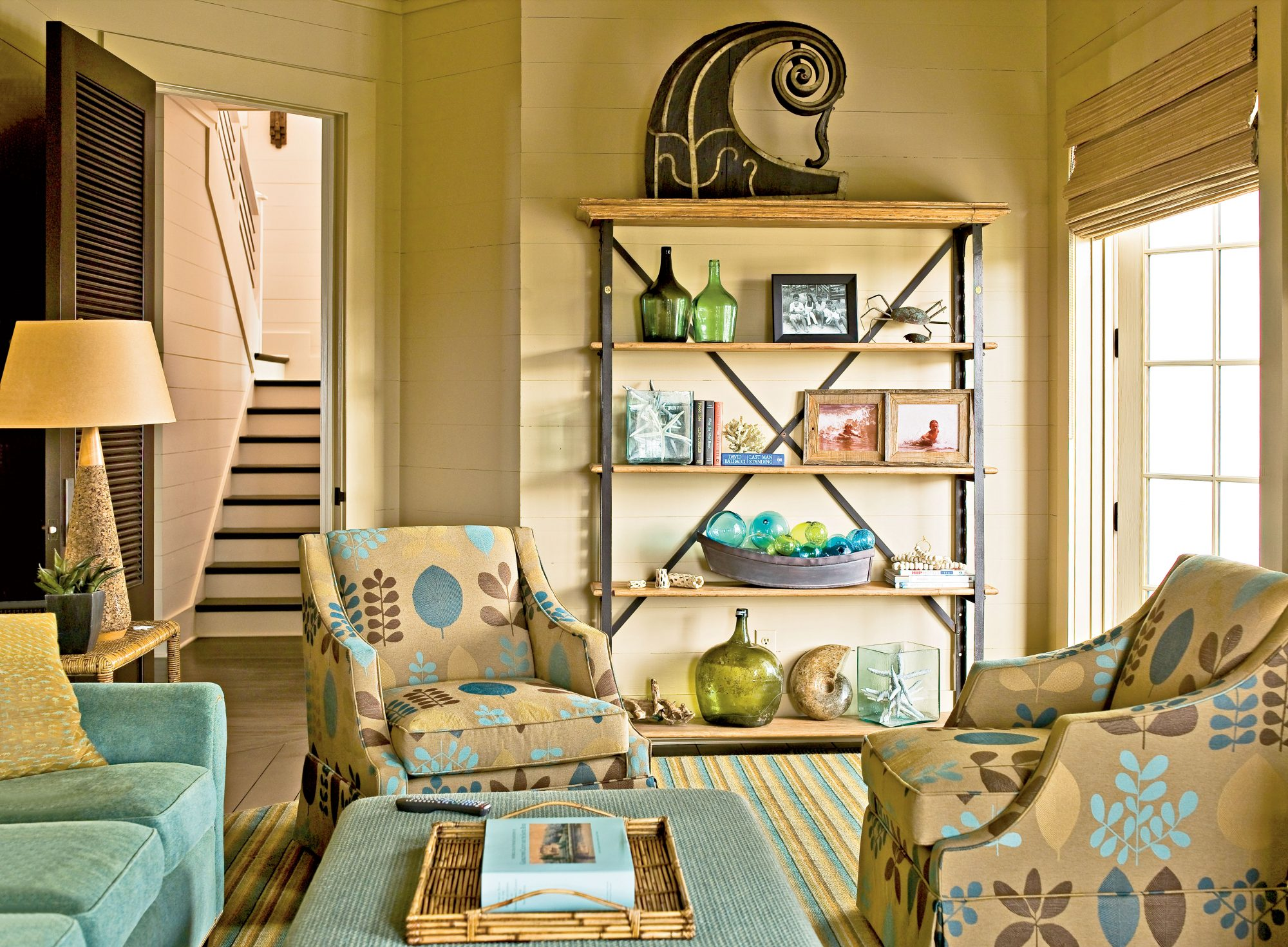 Pump up the excitement in your den with a quirky print and lighthearted decorative touches. As long as you continue with neutrals and natural elements, the effect will still be relaxed. The accessories, such as the glass bottles and balls lining the shelf, have a just-washed-up-on-the-shore feel.
