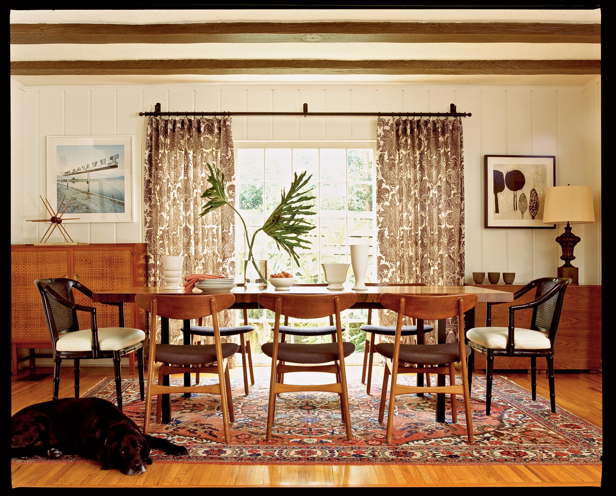 The quirky combinations in this chic dining room, like a Persian rug paired with chocolate and cream paisley curtains, only work because they're allowed to stand out. Meek prints need not apply!