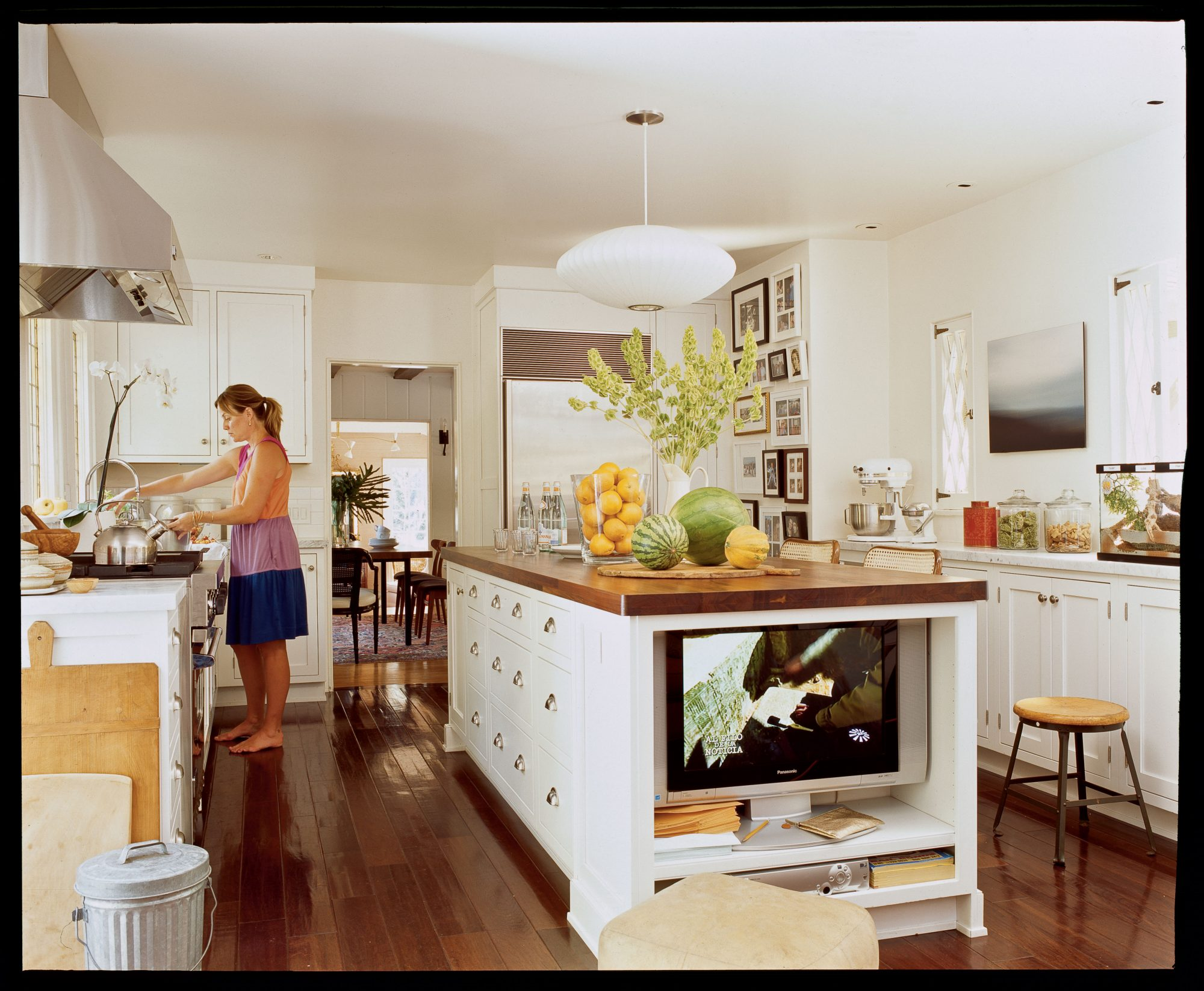 Get creative and save some much-needed space in the kitchen. This sizeable walnut-topped island does double duty as a TV stand, thanks to a handy nook on the end.