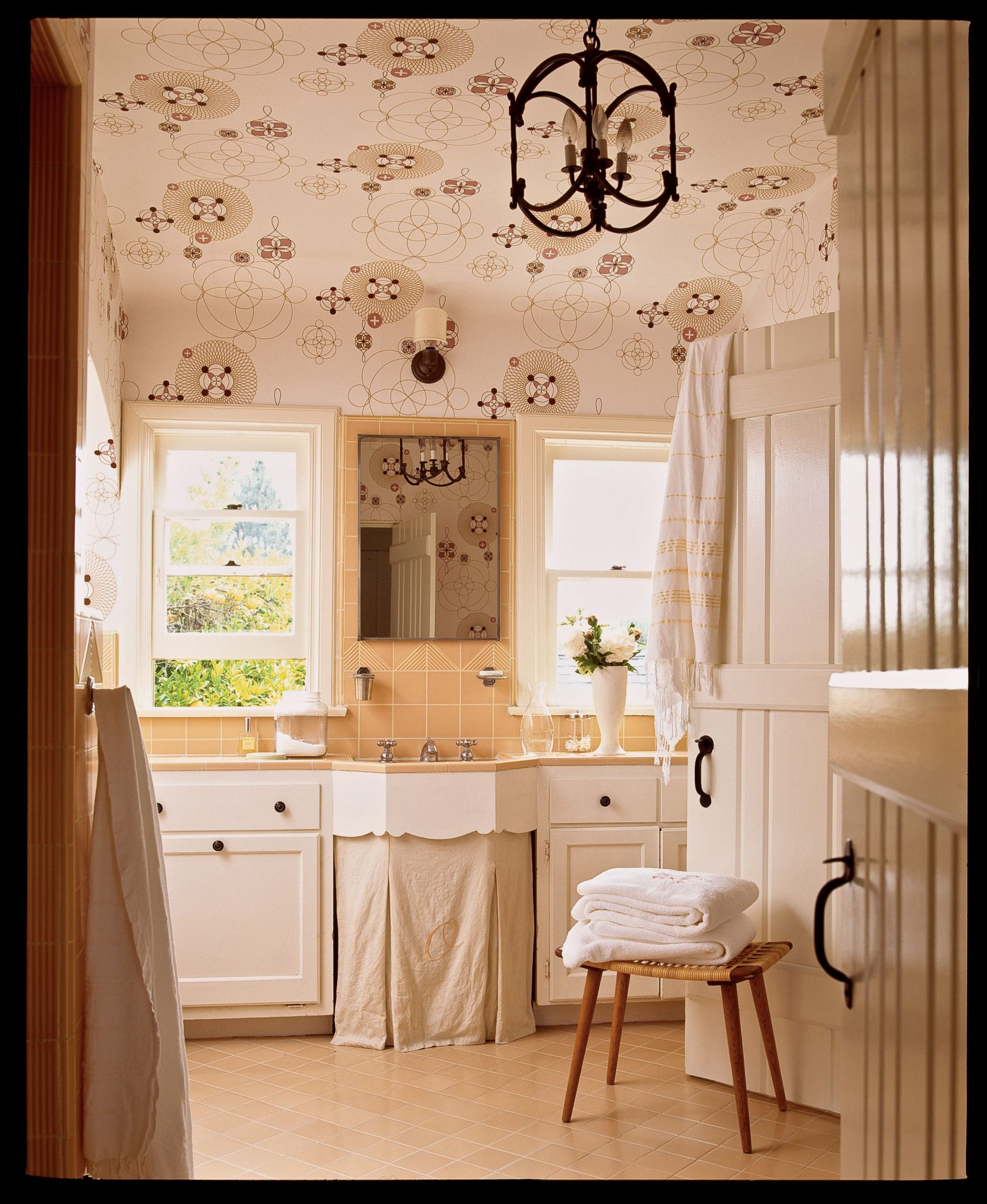 Itching for a renovation, but don't have lots of cash? The simple addition of whimsical wallpaper on the ceiling and walls diverts the focus from the retro peach tile and breathes new life into the room.