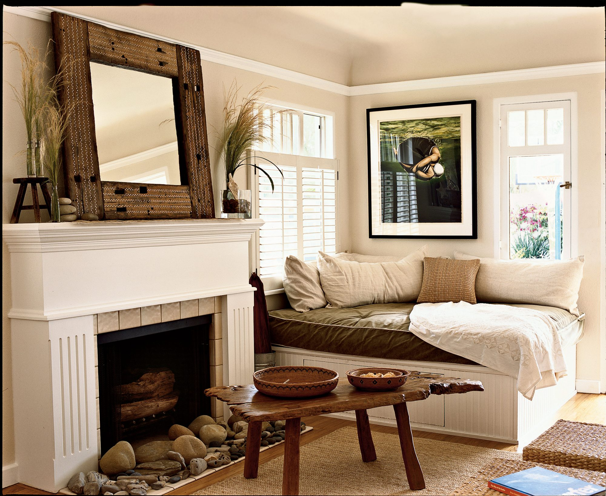 An extra-large cushioned space for lounging adds a quiet elegance to this simplistic living area. Organic extras such as the driftwood coffee table and decorative beach stones have a natural coastal charm.