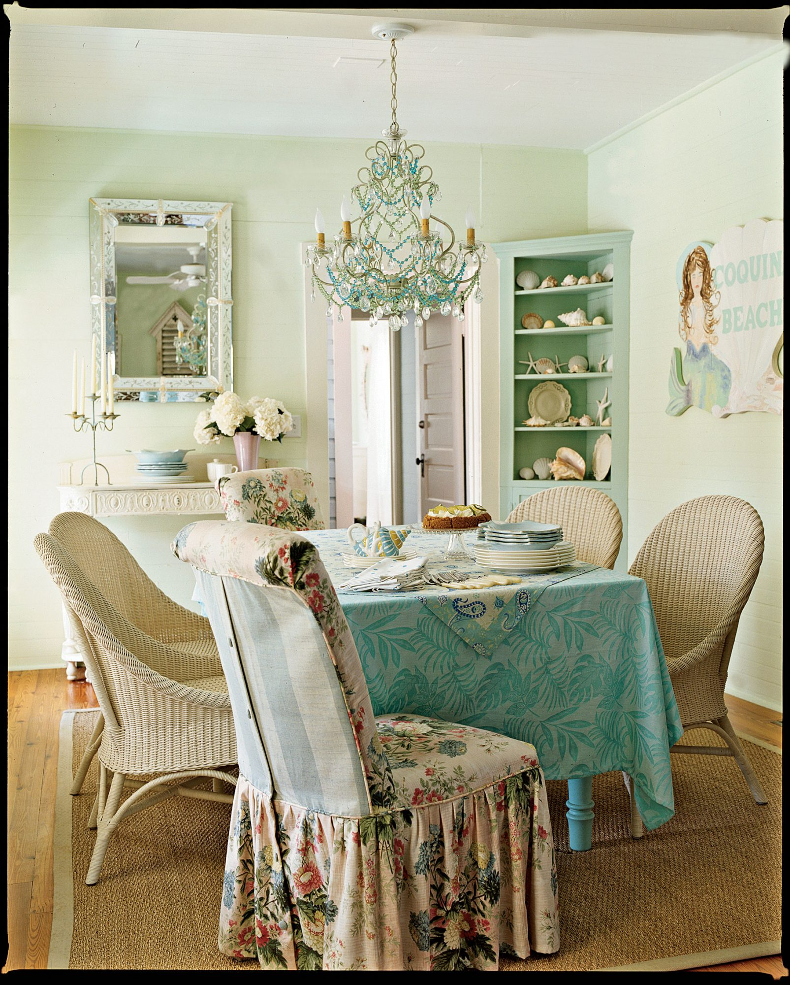 This sea-hued dining room strikes the ideal balance between formal and relaxed, with its fanciful chandelier and soft chintz slipcovers. Shells, sea stars, and a playful mermaid ensure that you won't forget you're at the beach.