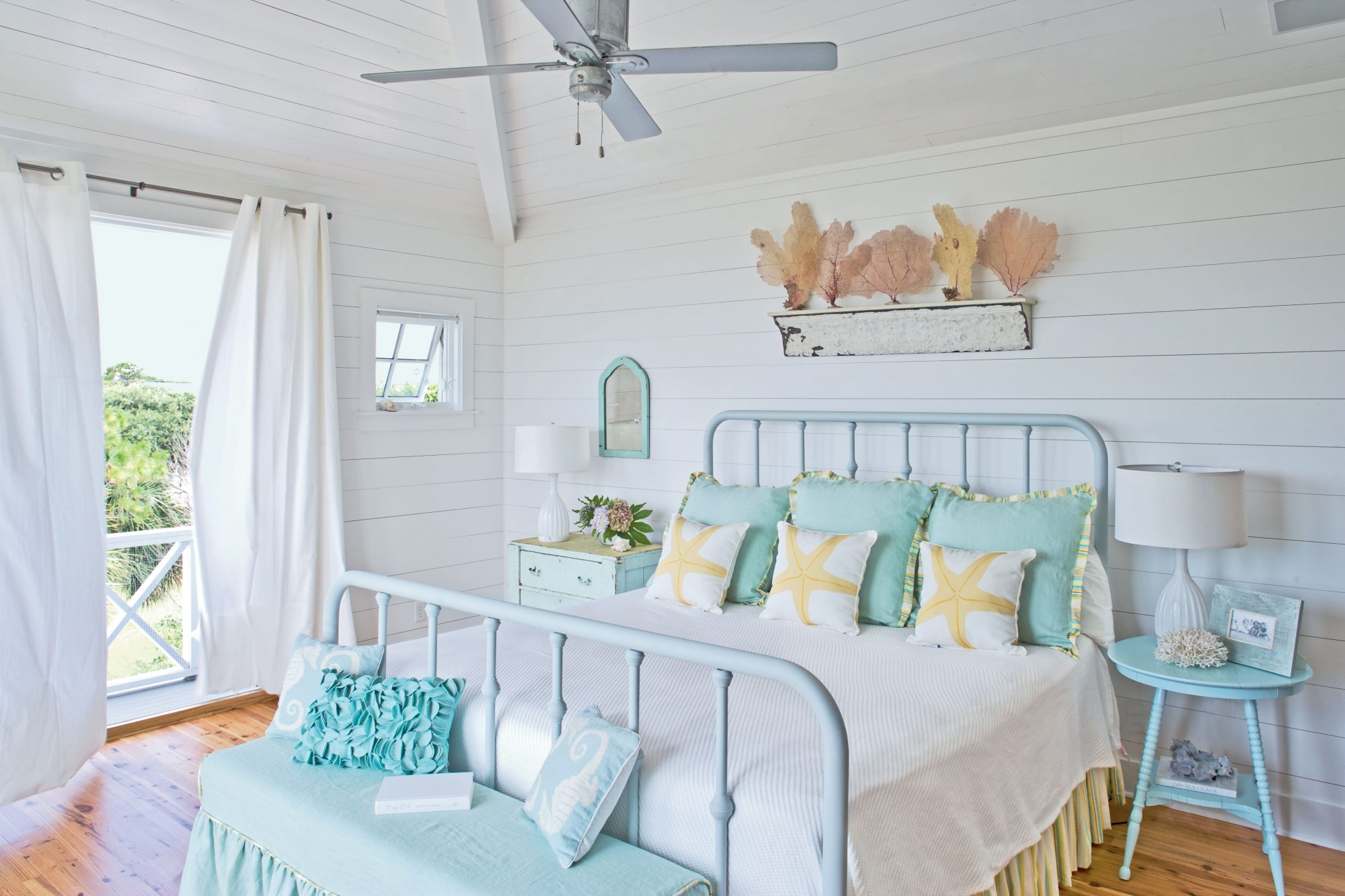 Soothing pastels have a universal appeal, especially in a coastal setting where relaxation is key. Colors that reflect the beach are a natural fit with these decorative coral accents and parading sea star pillows.