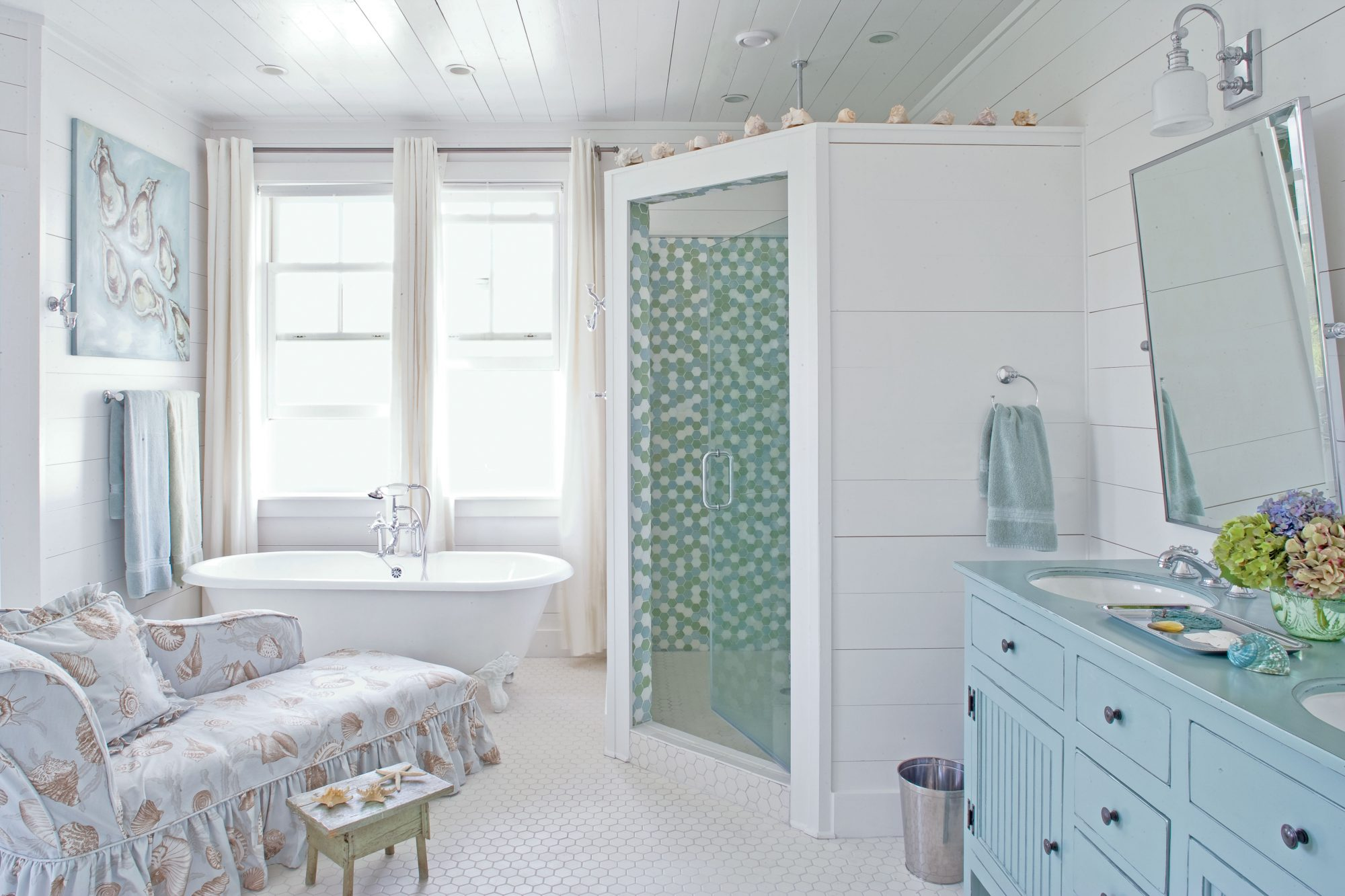 Take a bathroom from basic to basically your favorite room in the house! Surprise additions, like this shell-patterned chaise and vintage dresser-turned-vanity, insert a little luxury into your morning routine.