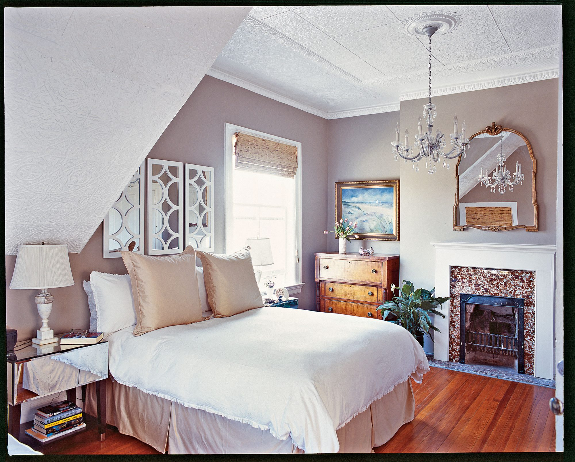 A lack of knickknacks, soft neutrals, and multiple mirrored surfaces make this tranquil master bedroom seem larger than its actual size. A hazy gray wall color is a chic alternative to bright white.