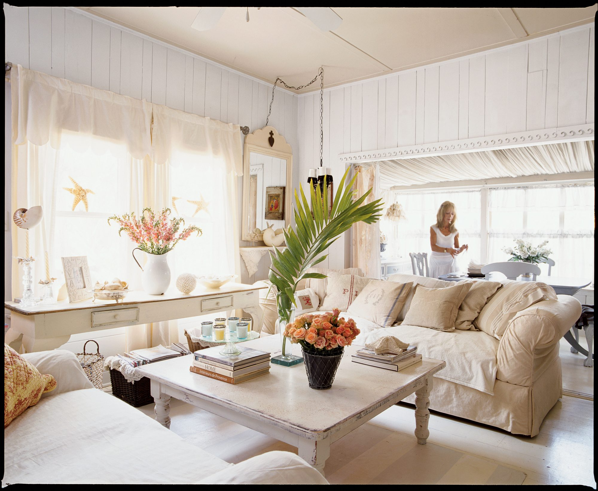 Lacy curtains, fresh florals, and plenty of monogrammed pillows are just a few of the feminine touches that give this room its calming and sweet mood. Pieces scored at thrift stores and flea markets were refreshed with paint, then artfully applied to achieve the shabby-chic distressed look.