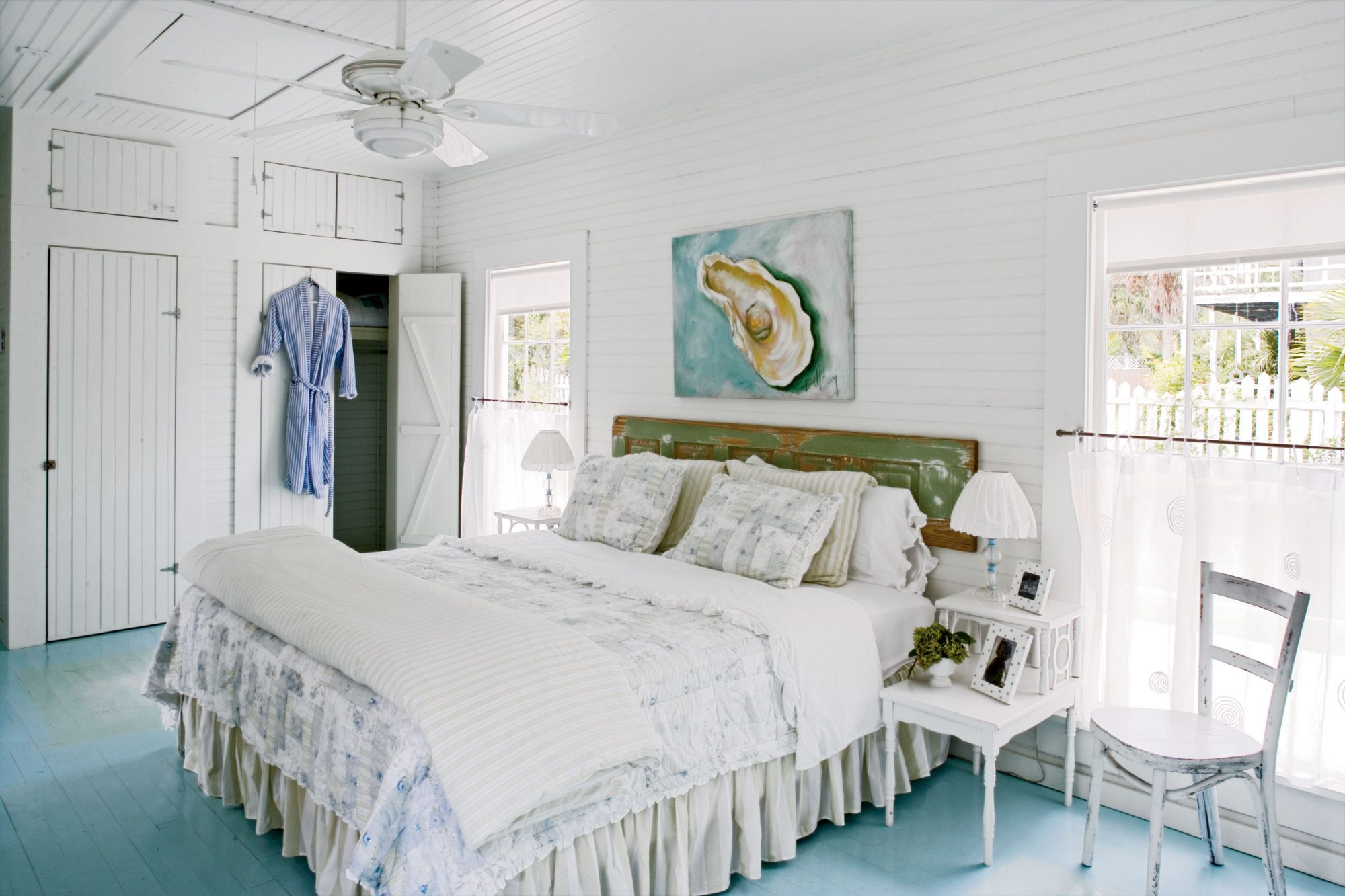 White beachy bedroom with wood white-washed closet doors and small side tables and chairs
