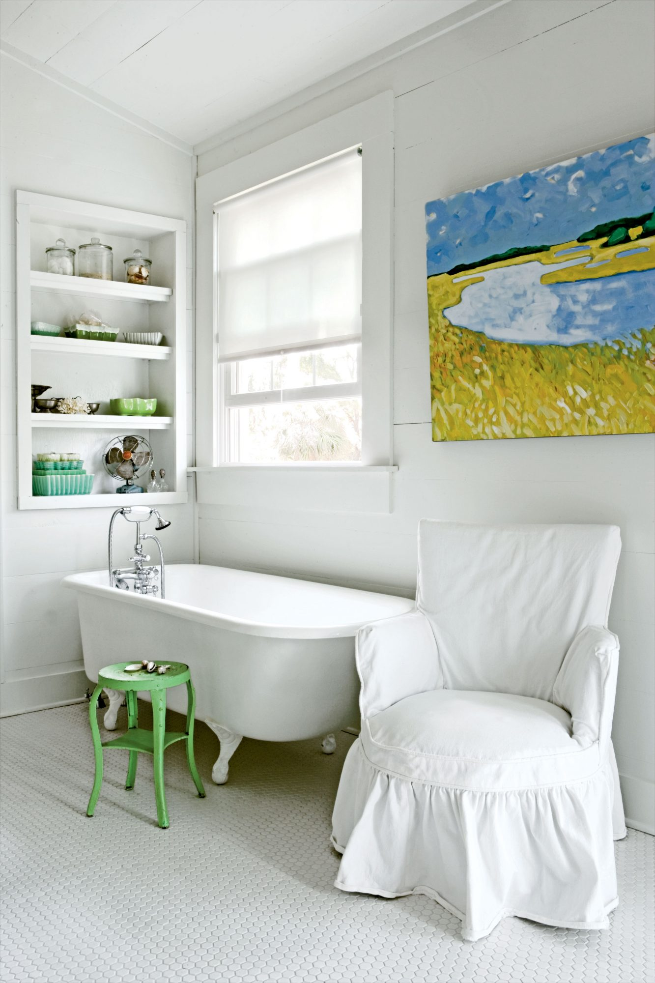 A blue and green water color painting is the focus of this simple white bathroom with a claw-footed tub, white slipcovered vanity seat, and small green stool
