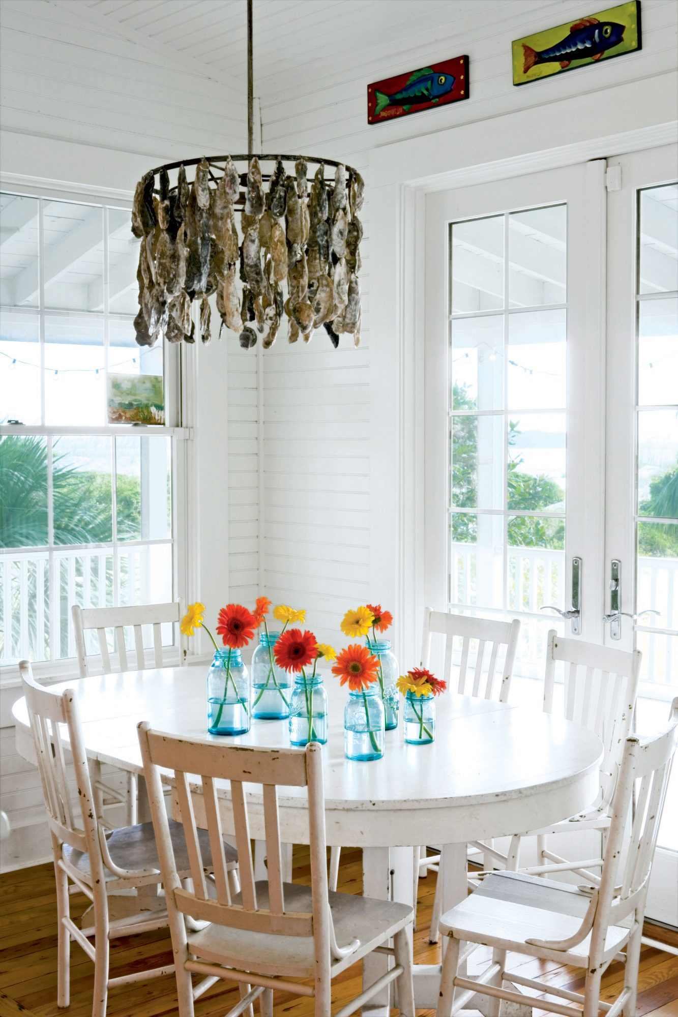 Leave the color to the landscape having a primarily white interior. The funky oyster-shell chandelier has the right amount of attitude to make sure this dining room doesn't look washed out.