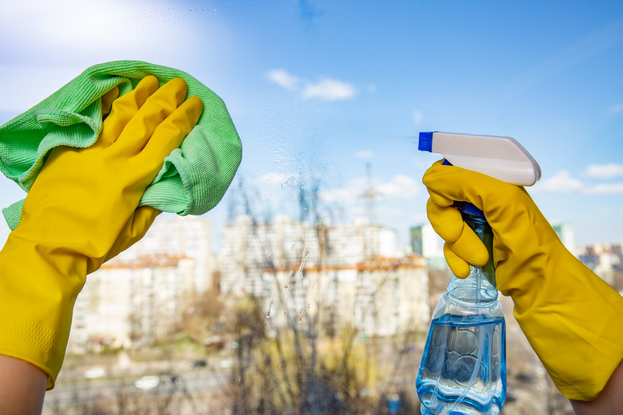 Female hands in yellow gloves cleaning window with green rag and spray detergent. Spring cleanup, housework concept