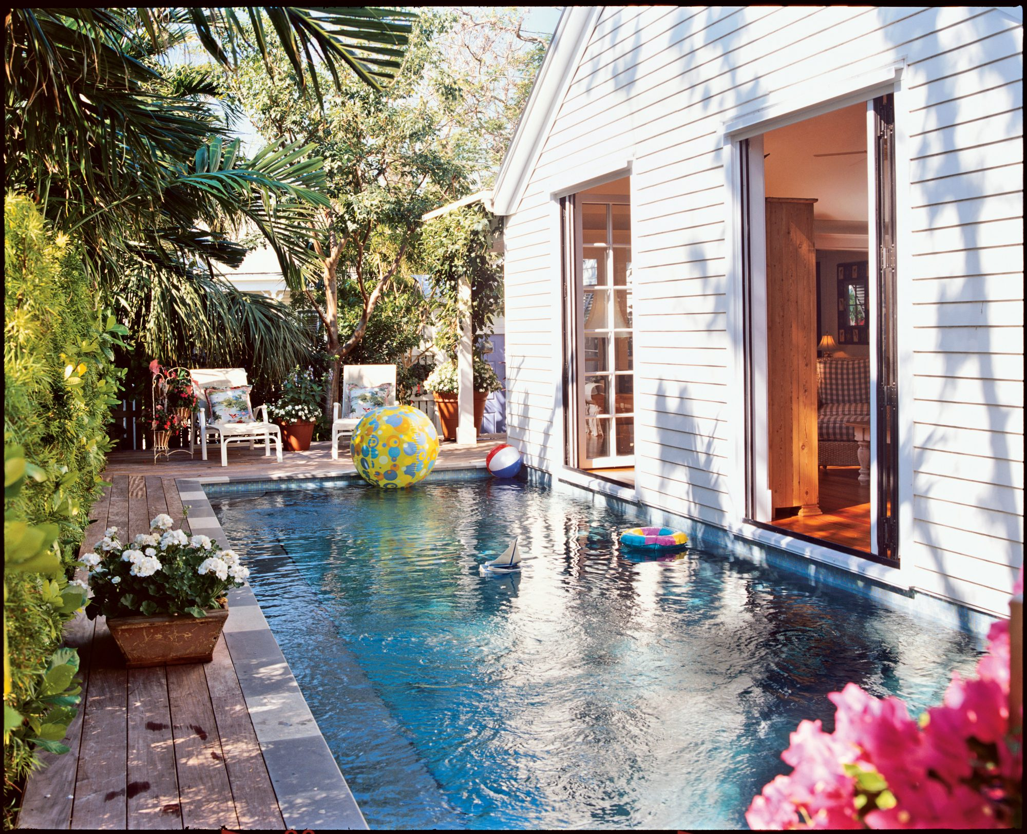"""One of the best features of this cottage is the pool, which shares a wall with the home's foundation. """"The pool's location was bred out of necessity,"""" the Carrs say. With two statuesque Spanish lime trees (a protected species) in the backyard, fitting a pool in was a bit of a challenge. But with the pool directly beside the house it becomes an extension of the living space."""