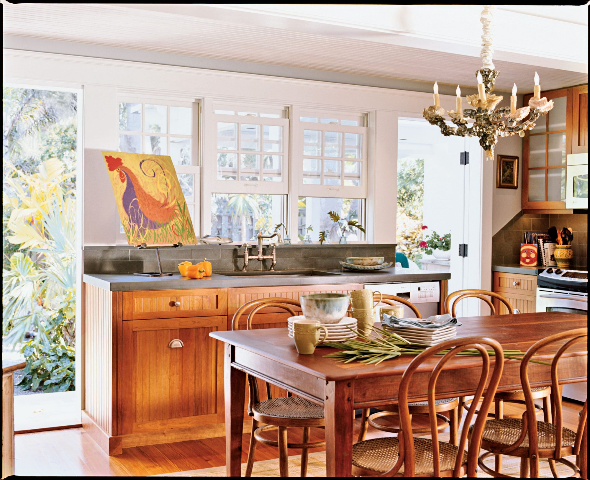 In the kitchen, a farm table and cherry cabinetry underscore the home's casual feel. Doors and windows open to the pool area, making it an ideal home for outdoor entertaining.