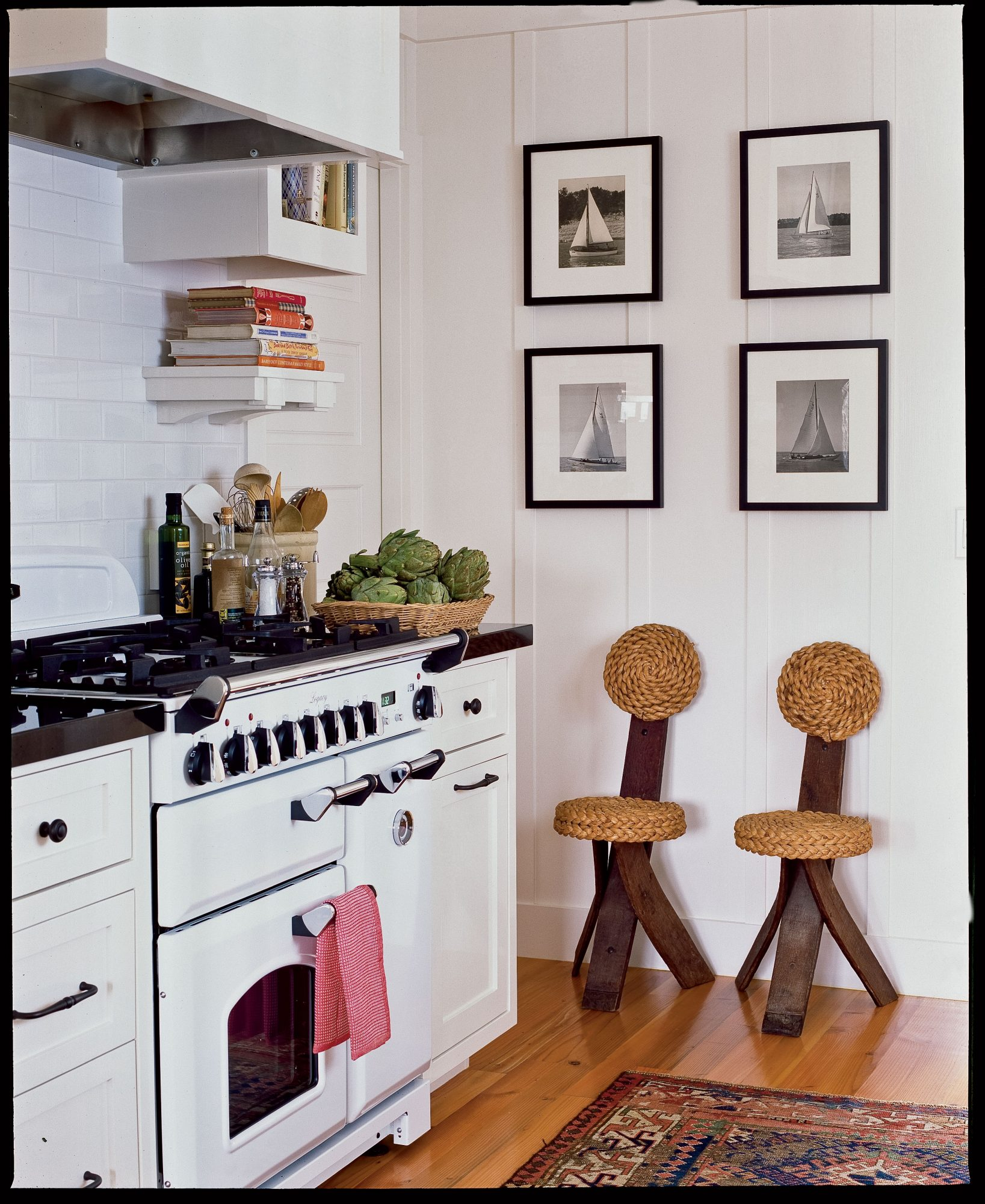 The kitchen's 1950s rope-and-wood chairs and the sailboat prints exude nautical style without being over the top. An Oriental rug covers the vintage Douglas fir floors in rich reds and blues, tying in the kitchen with the rest of the cottage.