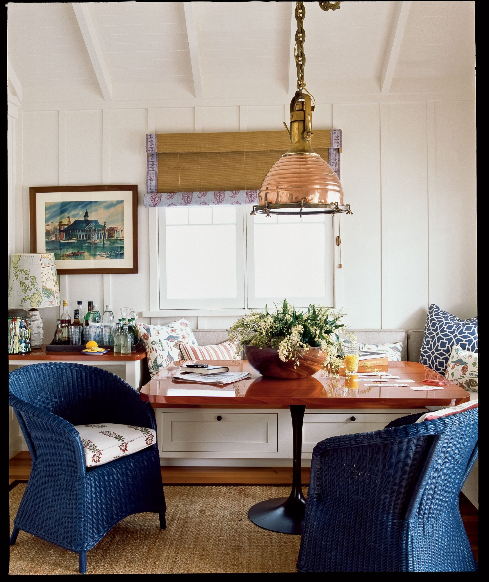 """Woven accents—a sea grass rug, a painted wicker chair—plus a few nautical nods, such as the brass pendant fixture, keep the mood casual and the focus on the water. """"This is the SoCal version of an East Coast fishing shack—everything is cozy and masculine; nothing is delicate,"""" the homeowner says."""