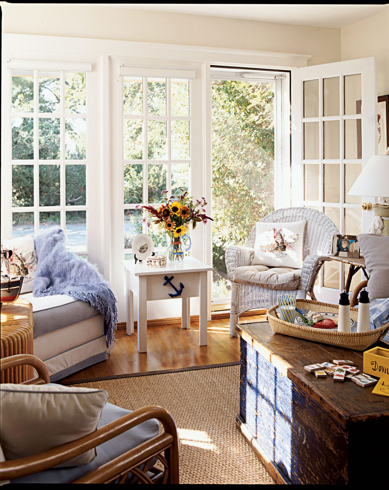 A sea grass rug, wicker and wood furniture, and plenty of streaming light from the French doors fill this sunroom. A few nautical accents recall the idyllic setting.