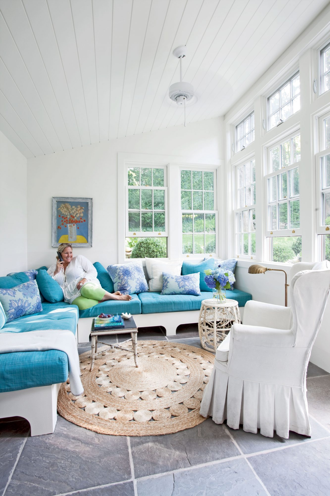 The homeowner uses her sunroom to curl up with a book or hang with friends, so comfy seating was a must. She had only an 11- by 13-foot area with which to work so she had her contractor build two benches for a space-saving and less expensive option than a sectional. She kept the room cheery and bright with fresh white paint on the walls and ceiling and bright blue cushions.